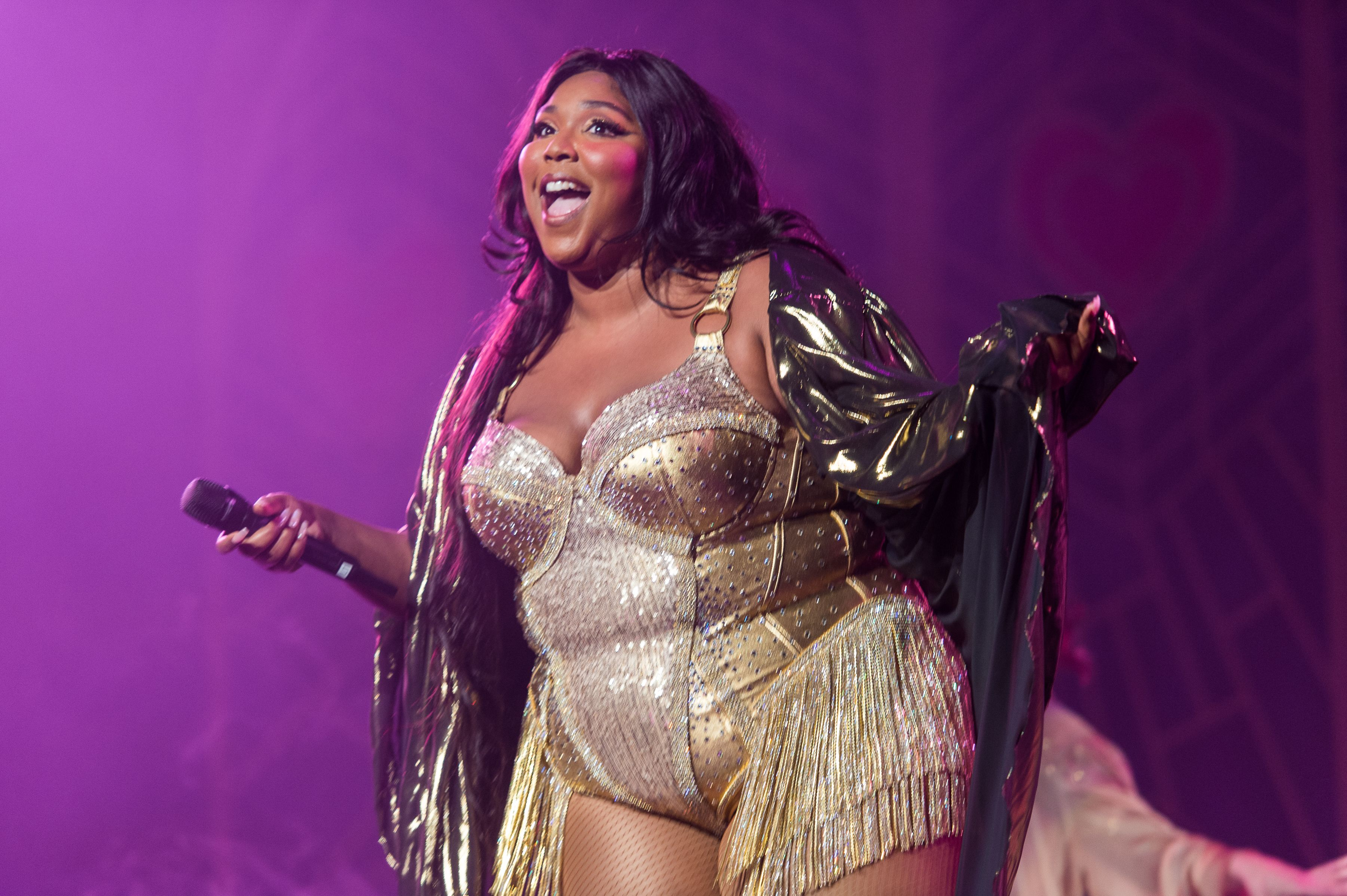 Lizzo rocks a gold fringe outfit on stage at a concert.