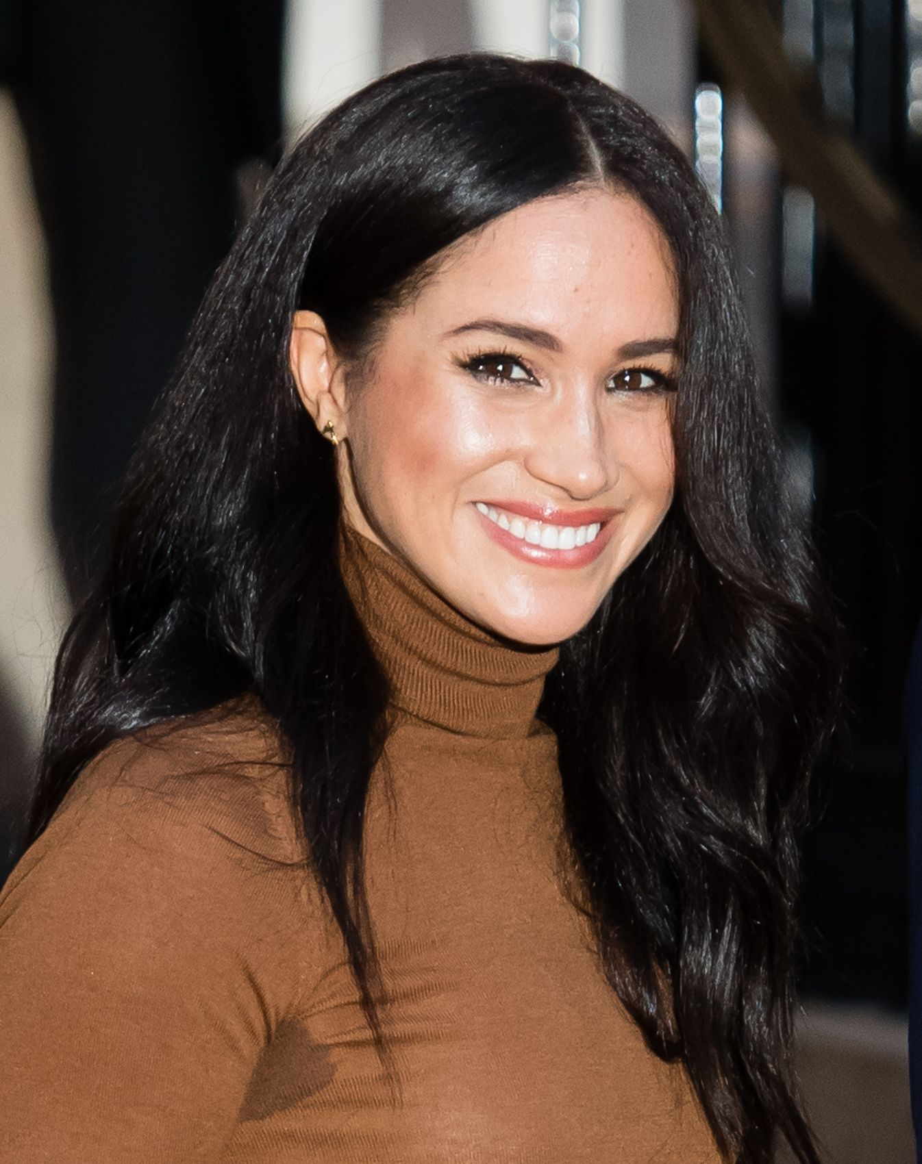 Meghan Markle smiles looking at the camera from an angle