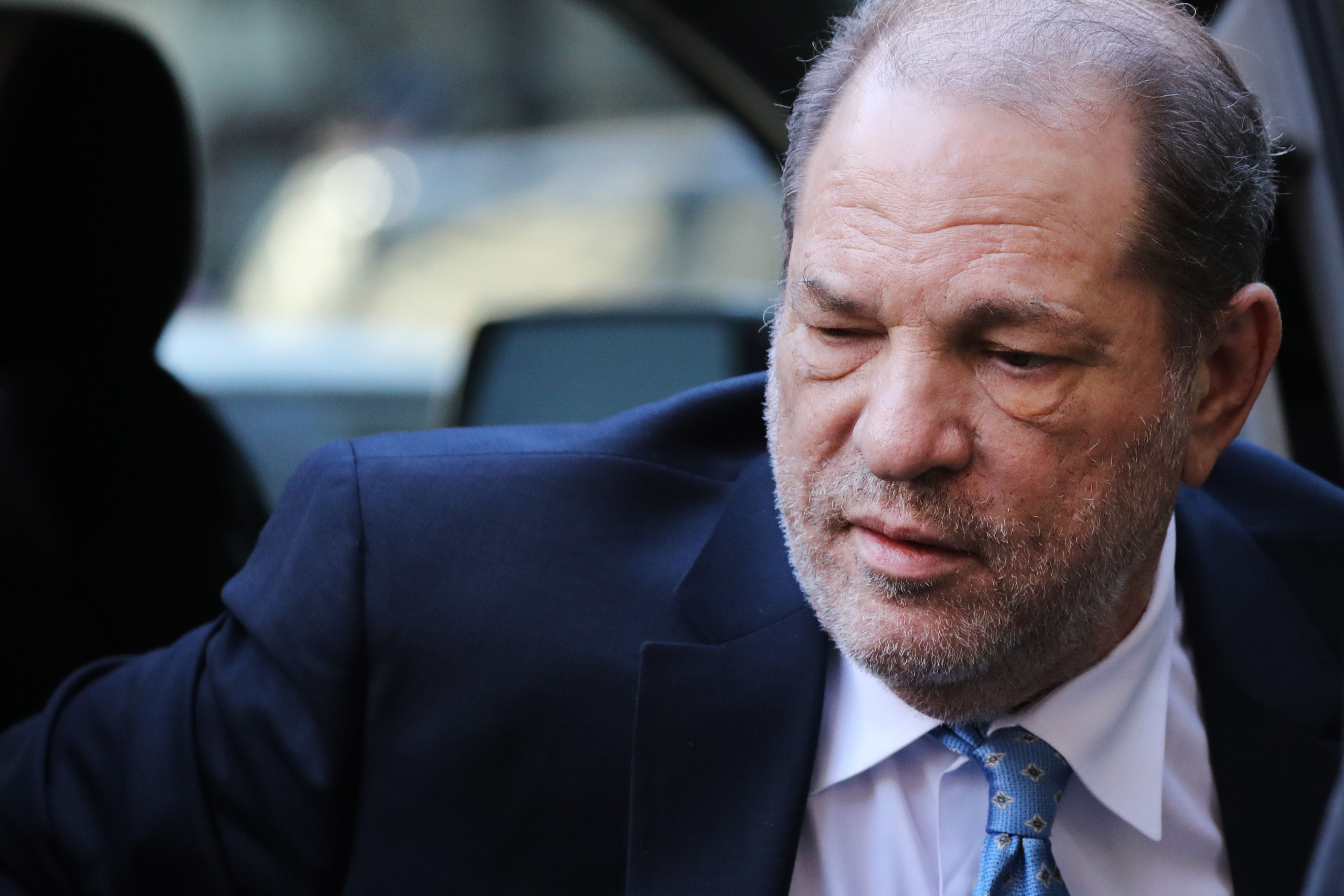 A photo of Harvey Weinstein coming out of a vehicle in a blue suit and poached tie.