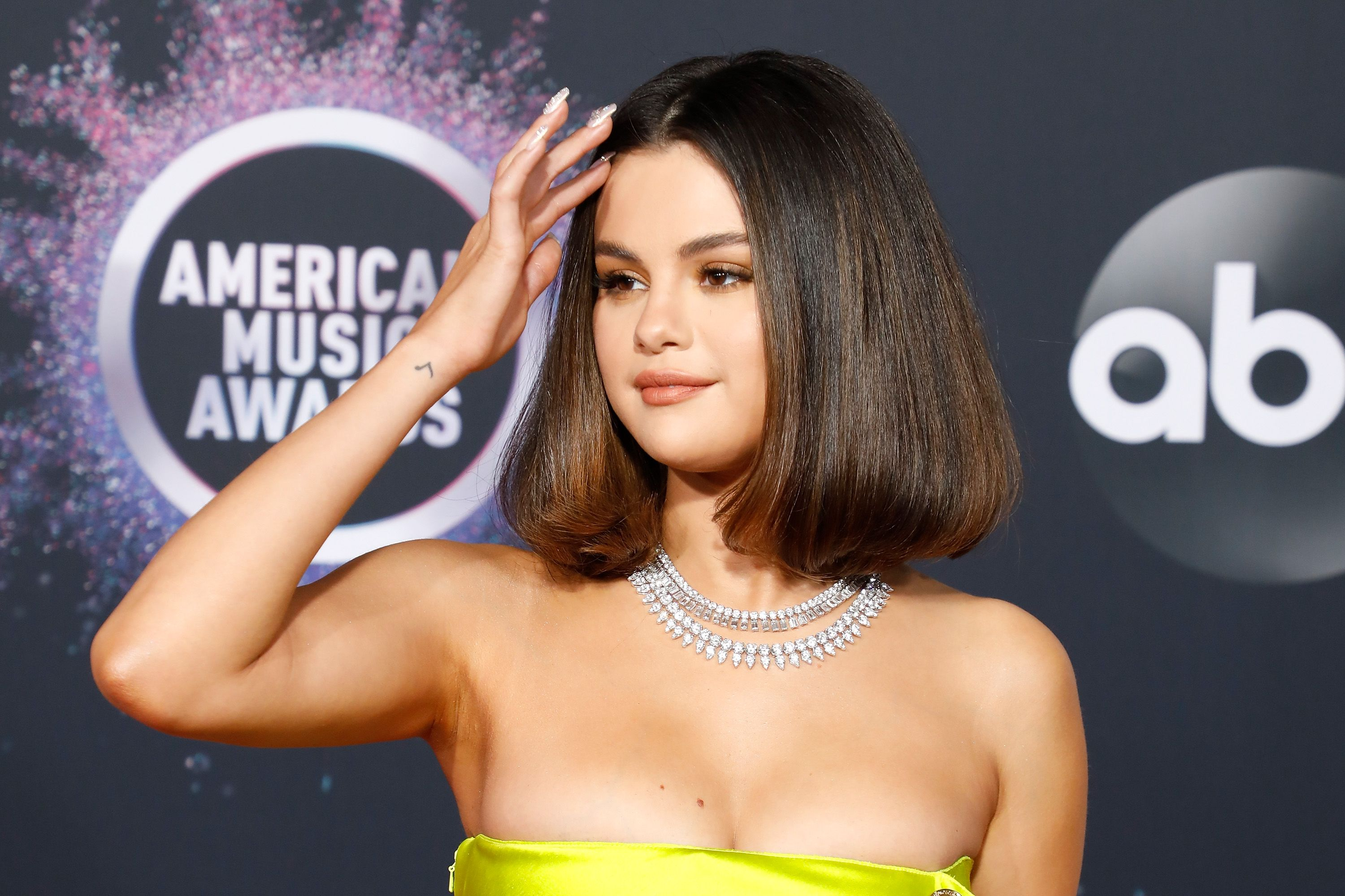 Selena Gomez poses on the red carpet fixing her hair