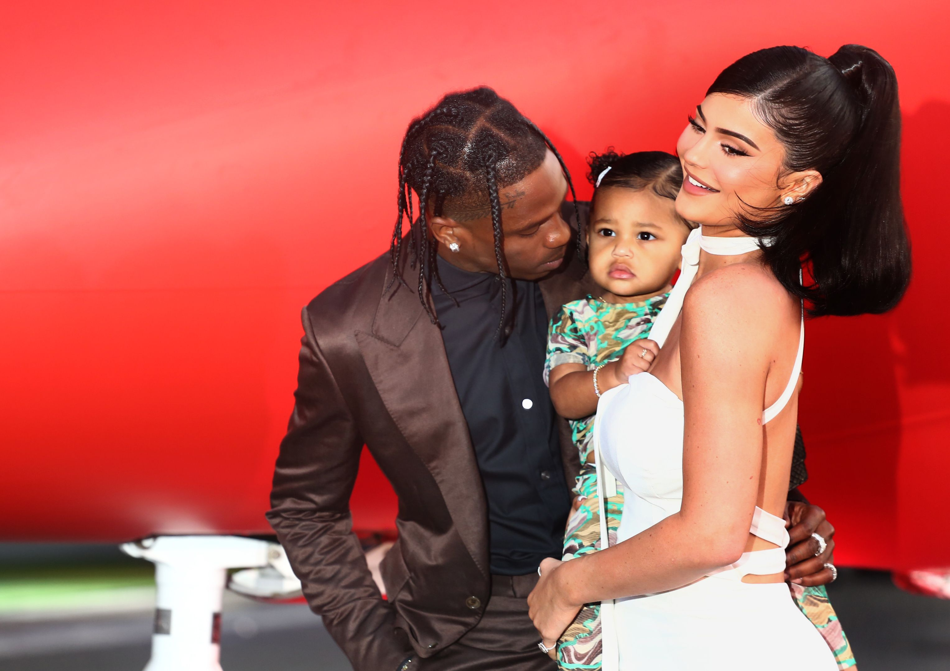 Travis Scott (left) puts his arm around Kylie Jenner (right) who is holding Stormi