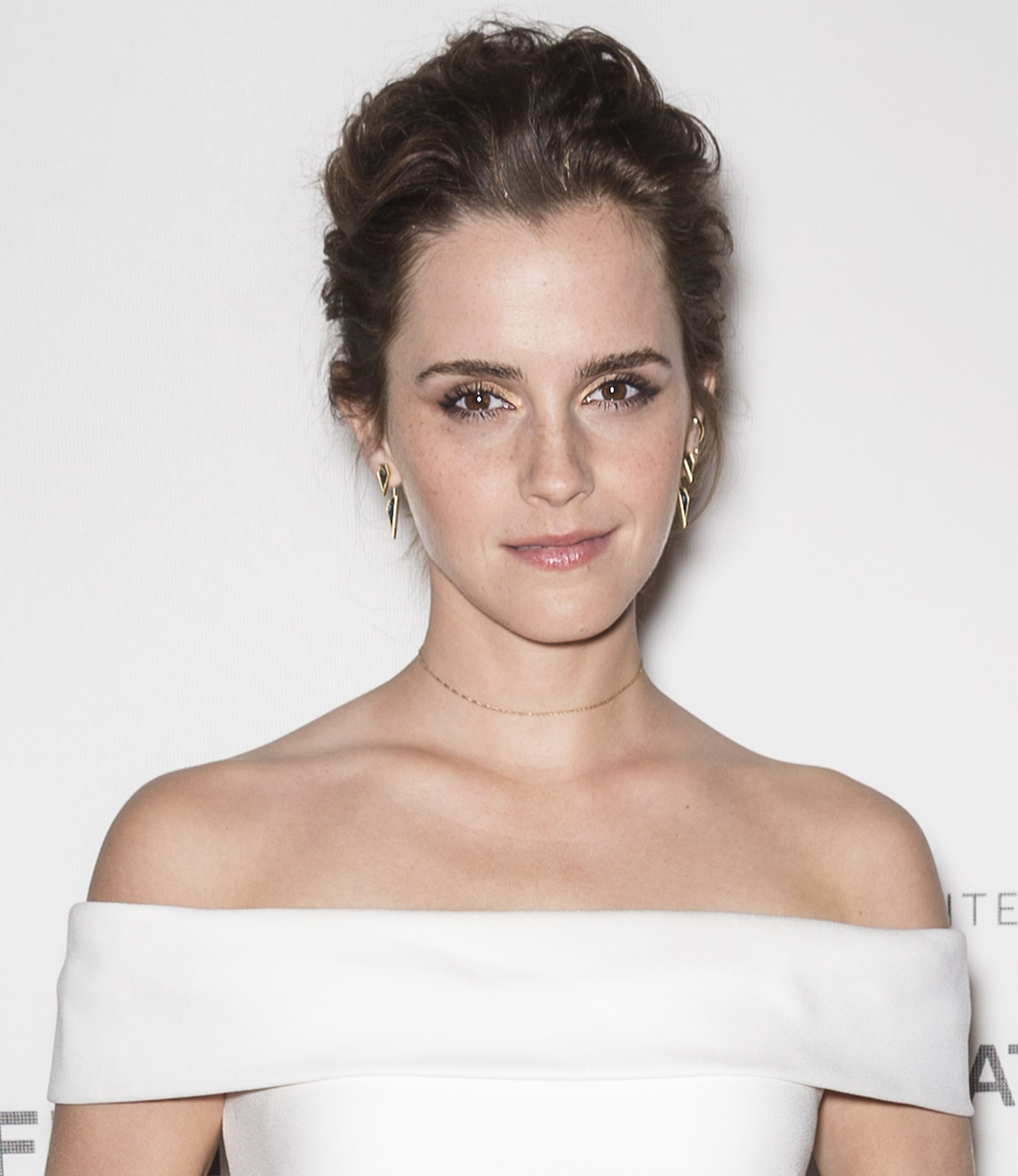 Emma Watson wears a white off the shoulder gown.
