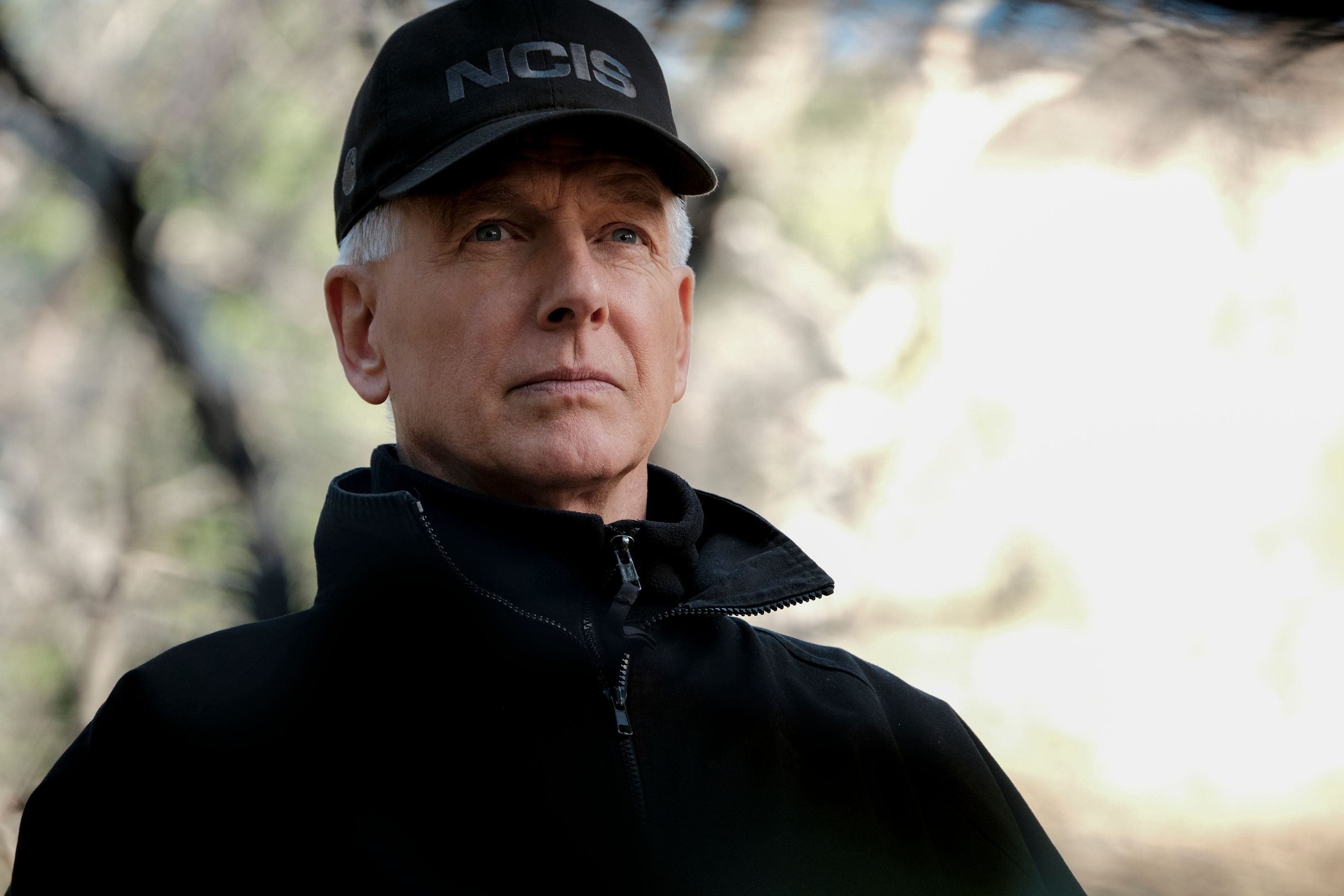 A man wearing an NCIS cap stares into the camera.