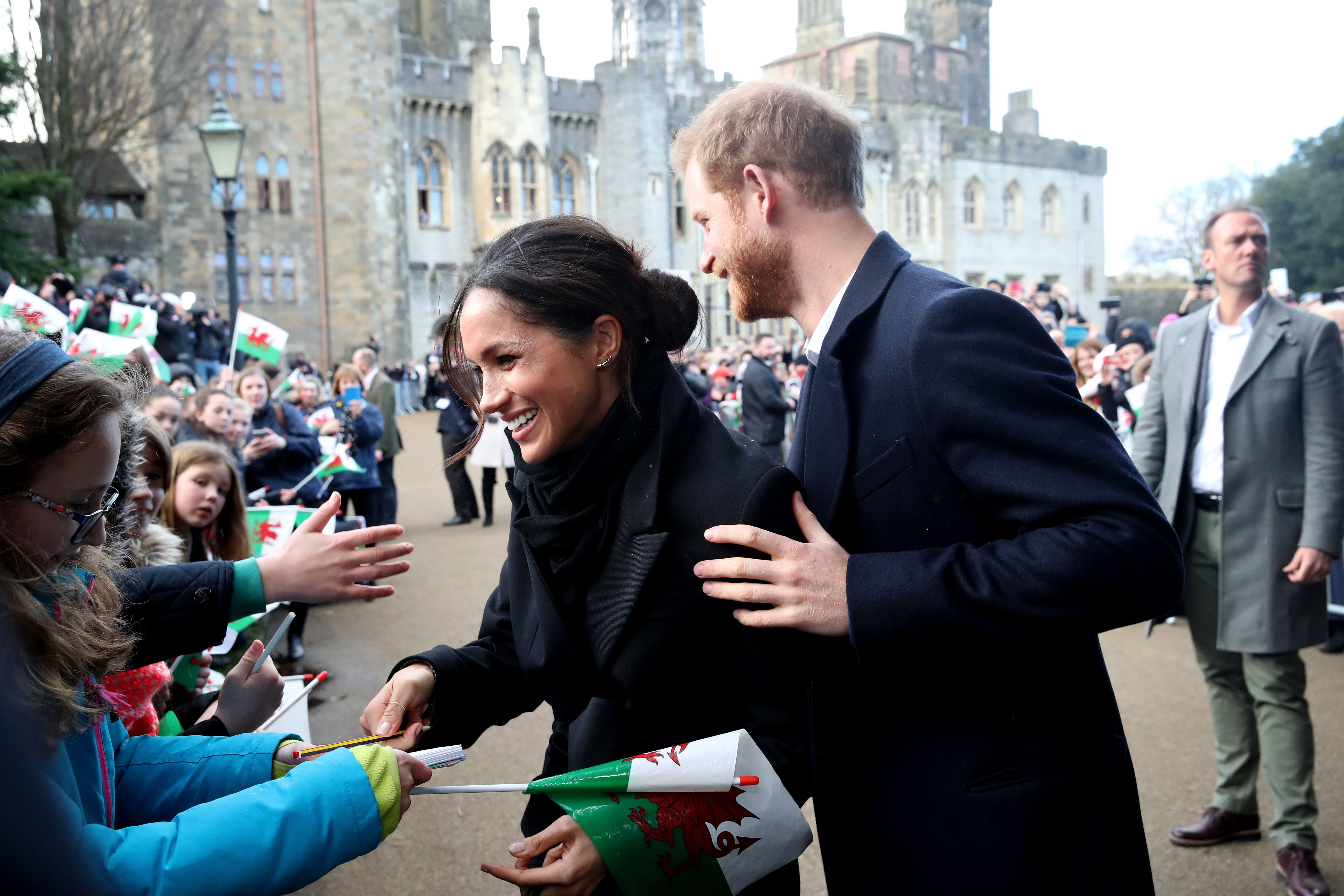 Prince Harry and Meghan Markle greeting crowds during an engagement