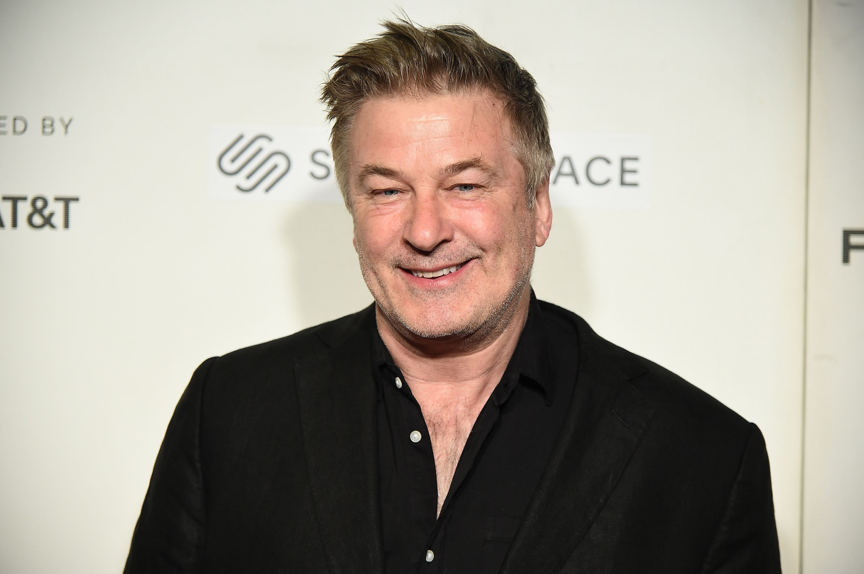 Alec Baldwin looks amazing in this black T-shirt and the smile on his face is gorgeous.