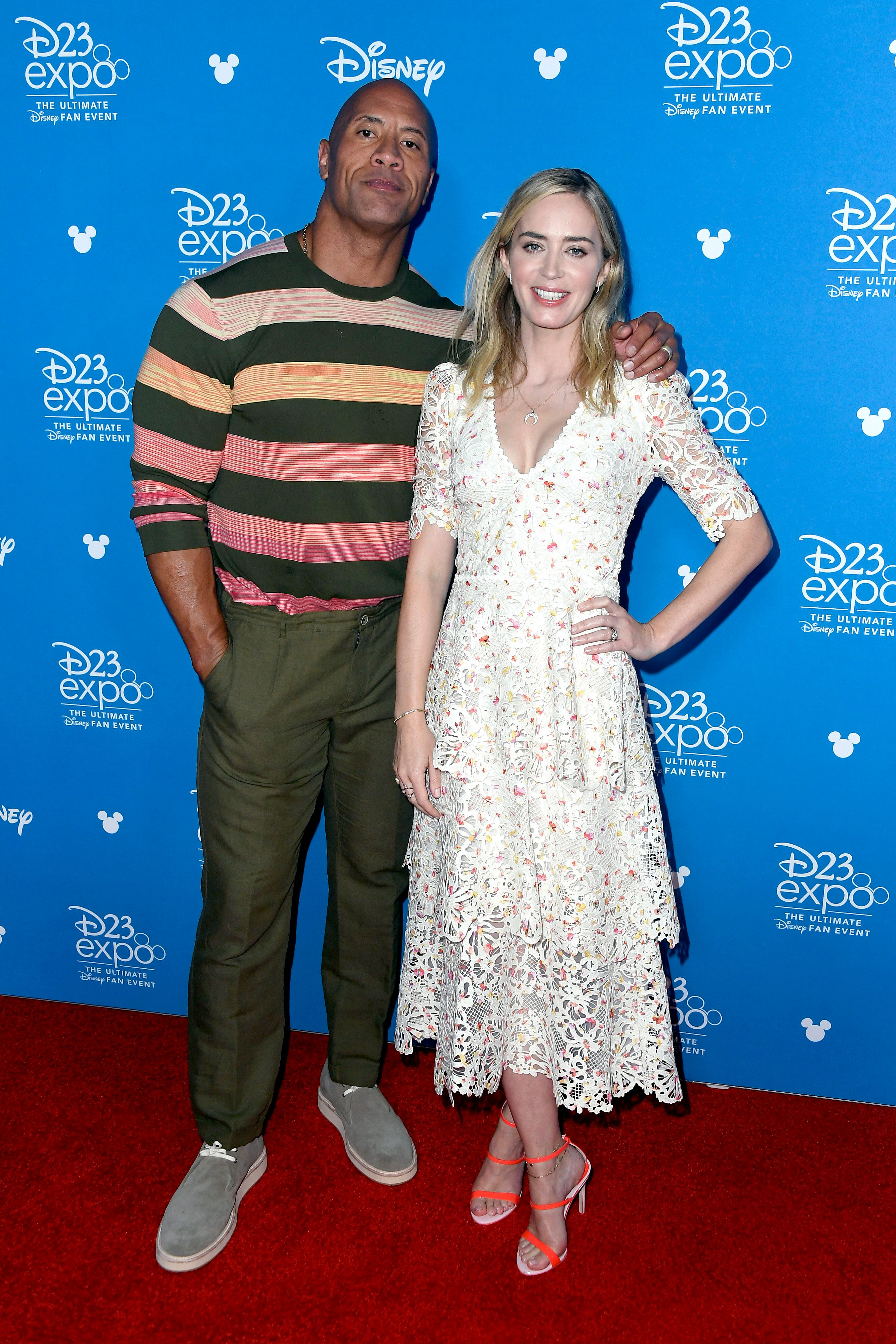 Dwayne 'The Rock' Johnson stands in a striped shirt with Emily Blunt in a white dress with flowers.