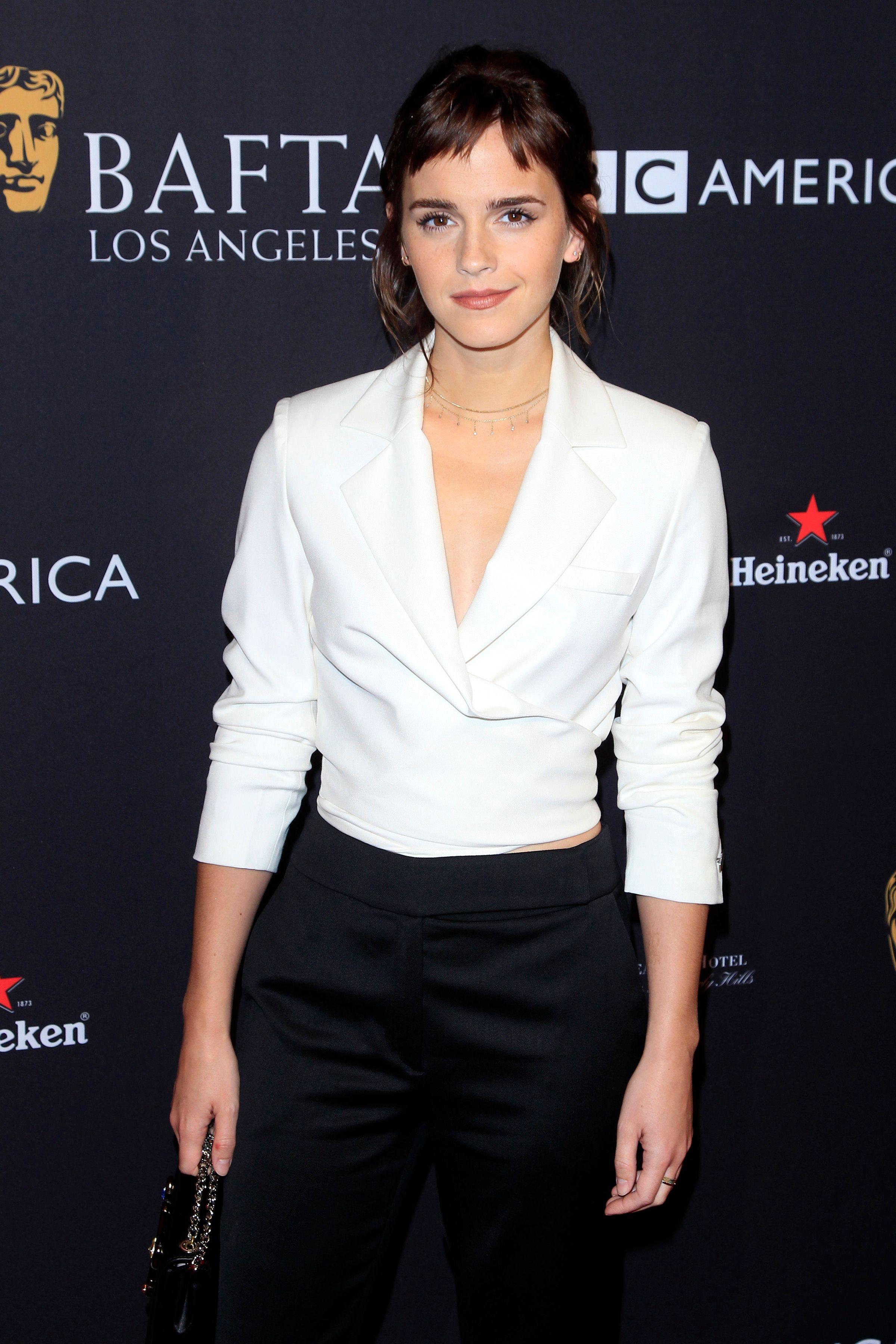Emma Watson wears a white shirt and black pants.