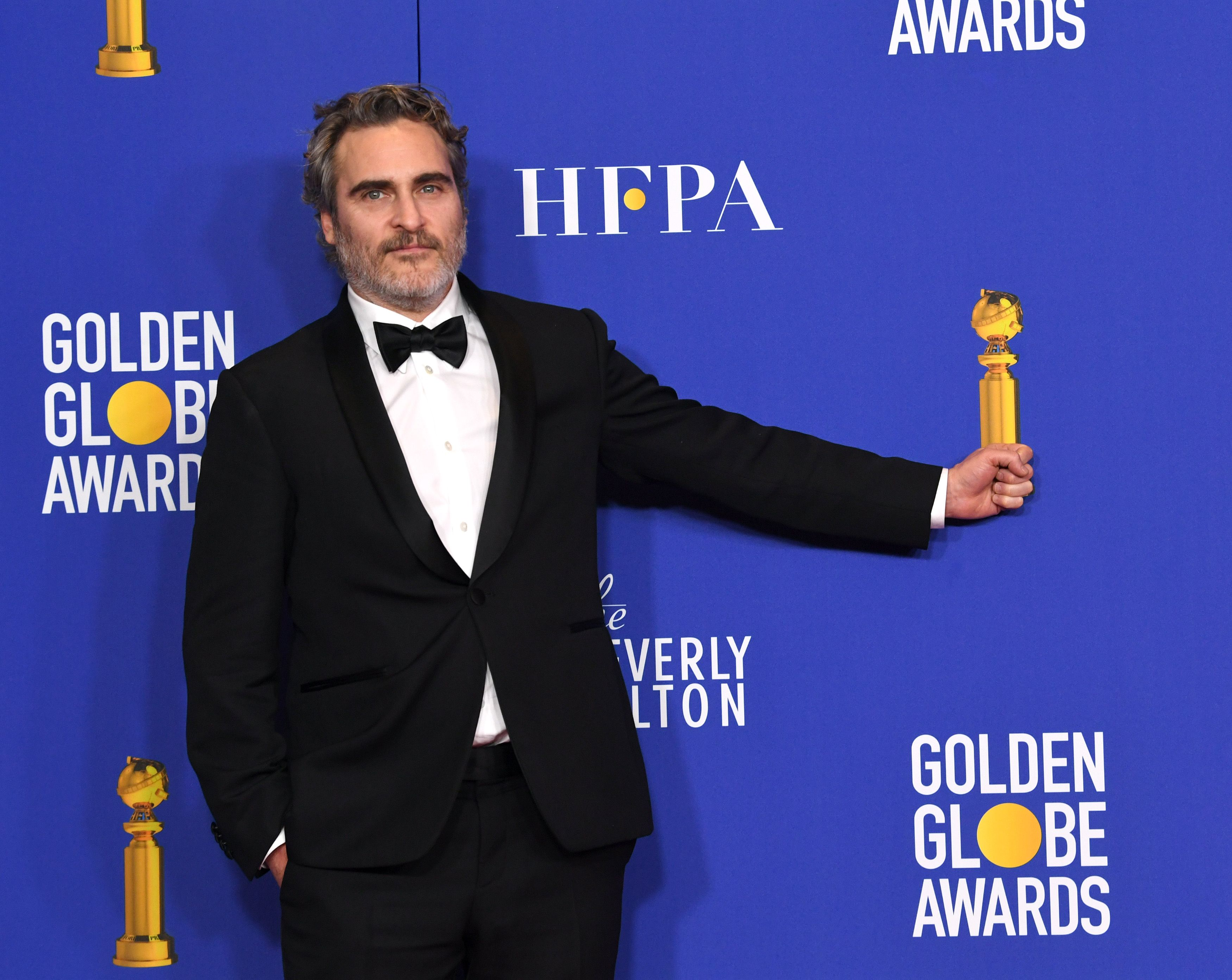 Joaquin Phoenix holding his Golden Globe