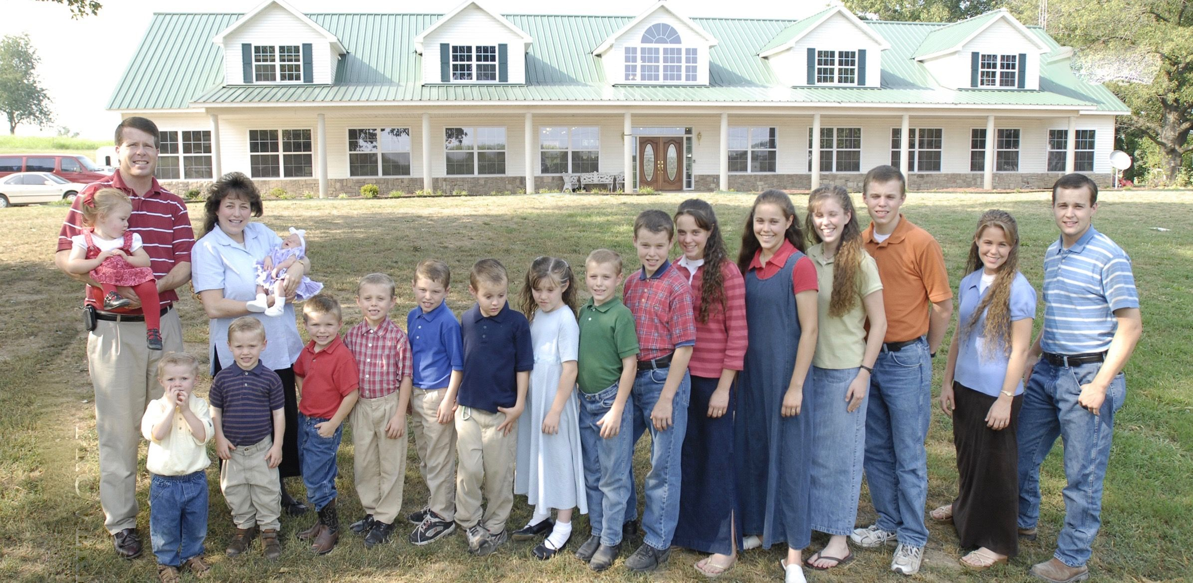 The Duggar family standing outside home