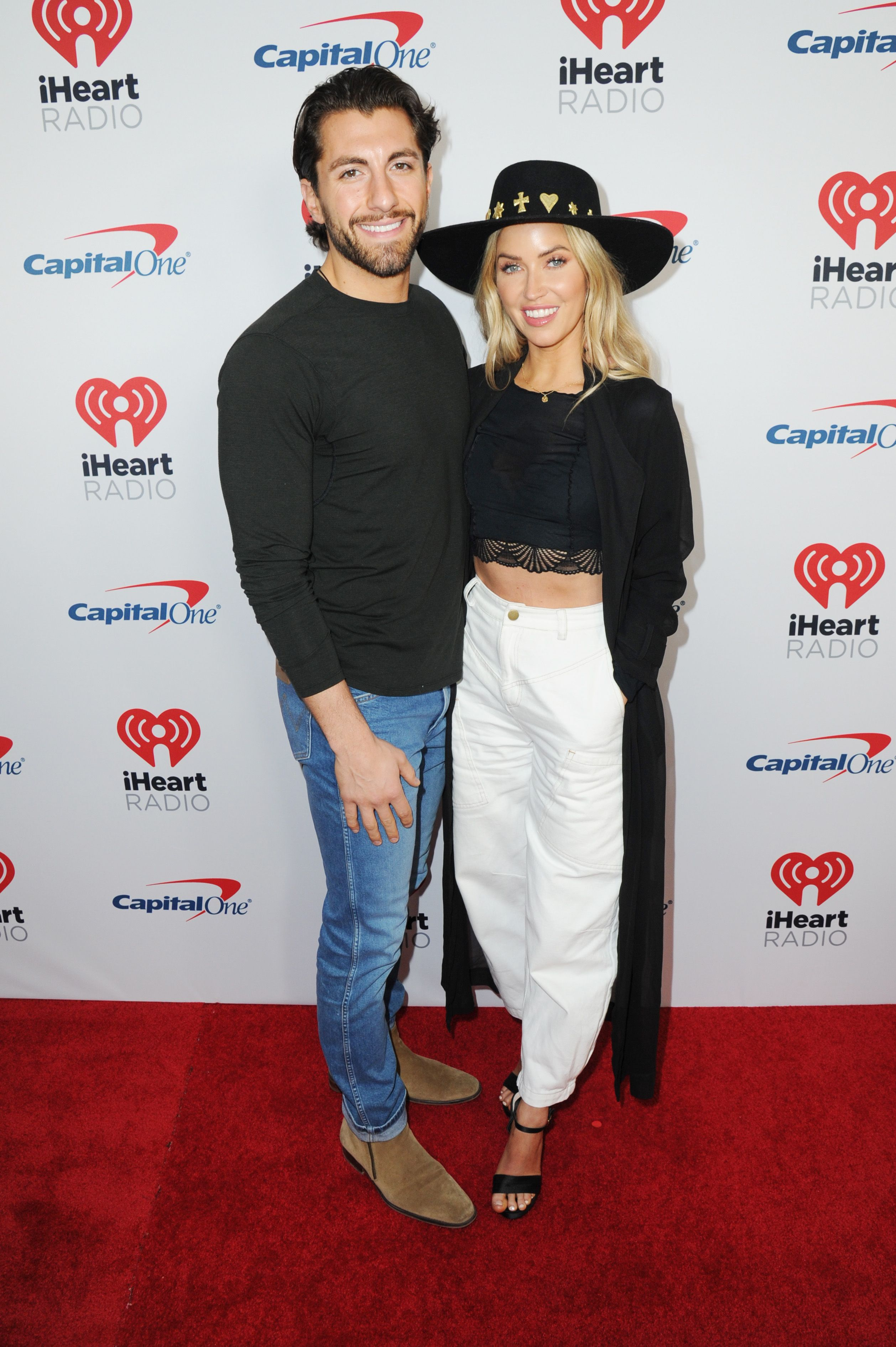 Kaitlyn Bristowe wears white pants and a black hat next to Jason Tartick.