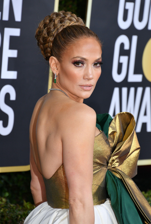 Jennifer Lopez headshot, hair updo, gold and white dress.