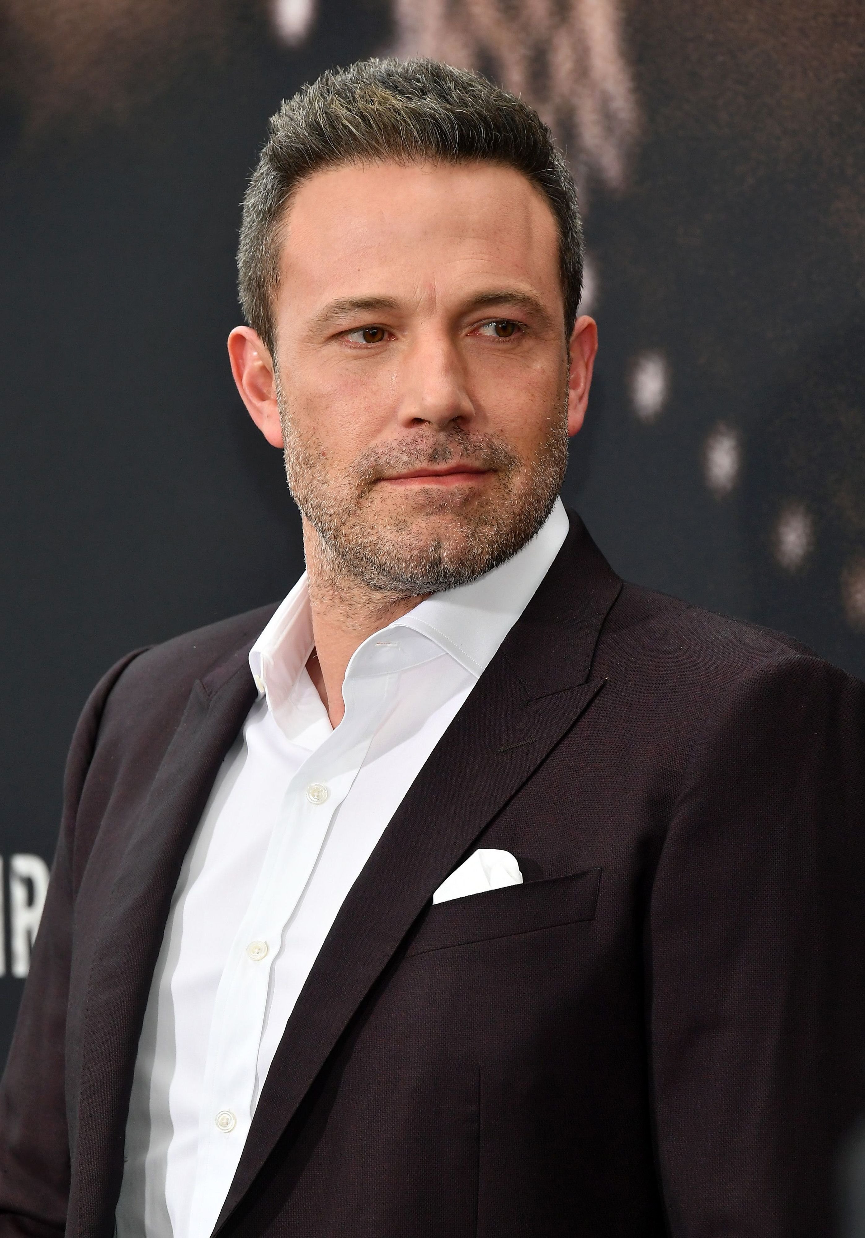 Ben Affleck poses on the red carpet looking off to the left