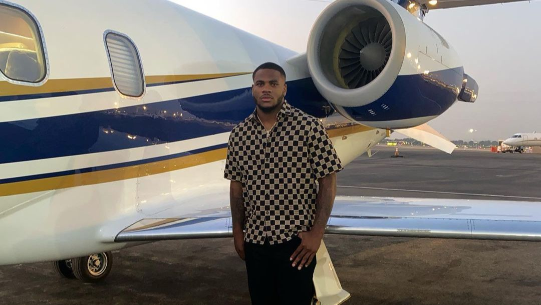 Micah Parsons standing in front of a private jet.
