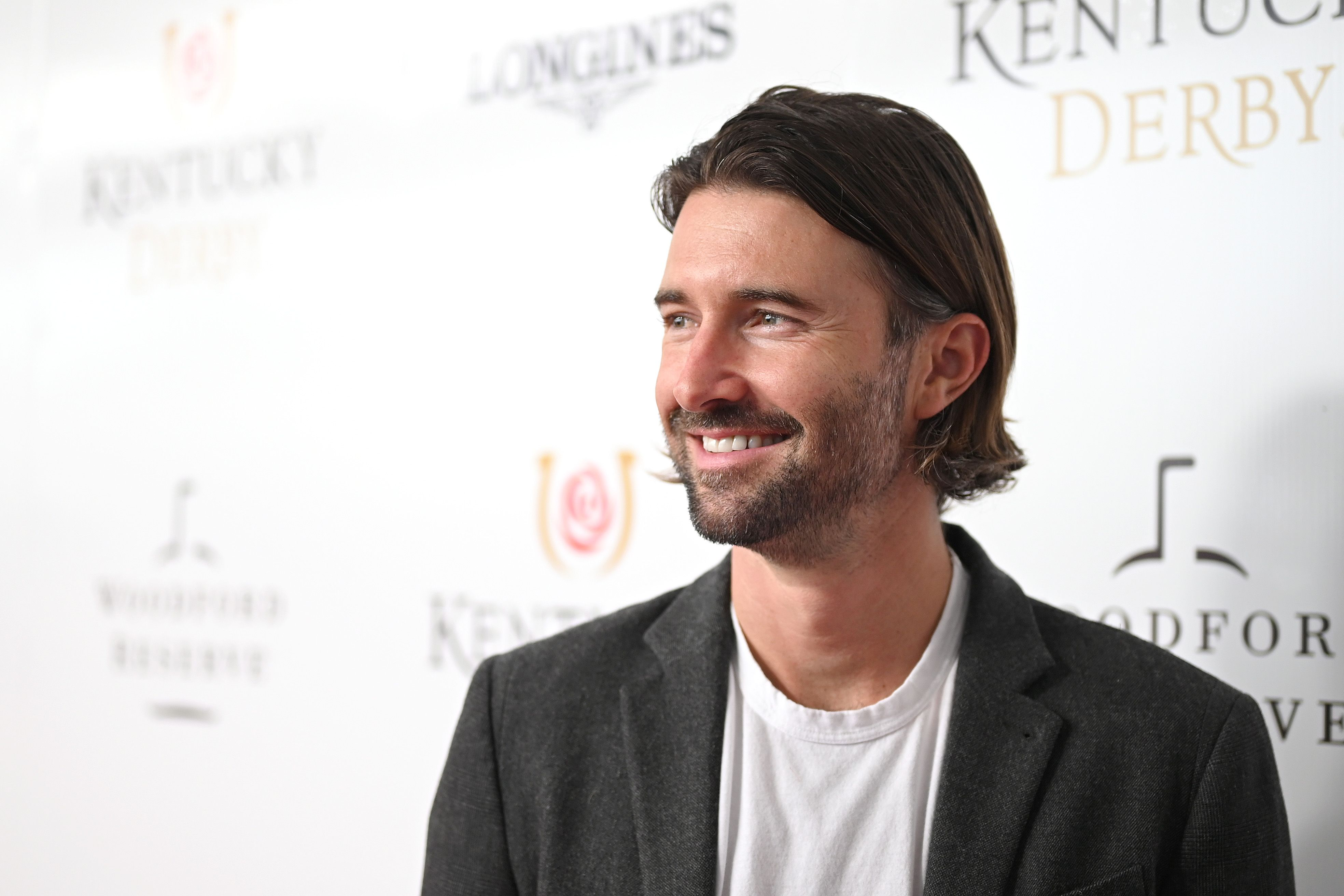 A photo of Brandon Jenner sporting a grey suit and white inner round-neck at an event, and the smile on his face is gorgeous.