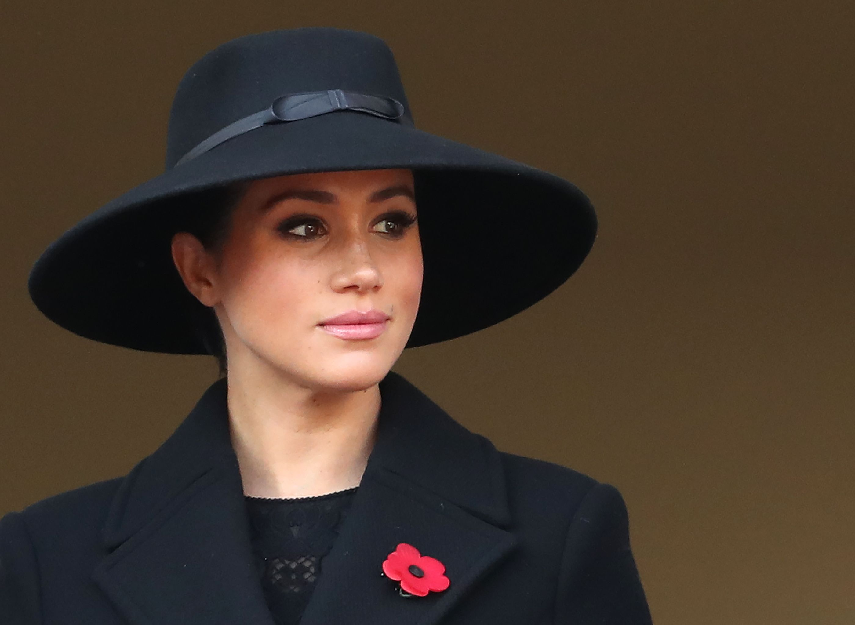 Meghan Markle looks off to the right of the camera posing in front of a brown background. She wears a black hat and jacket with a red flower pin