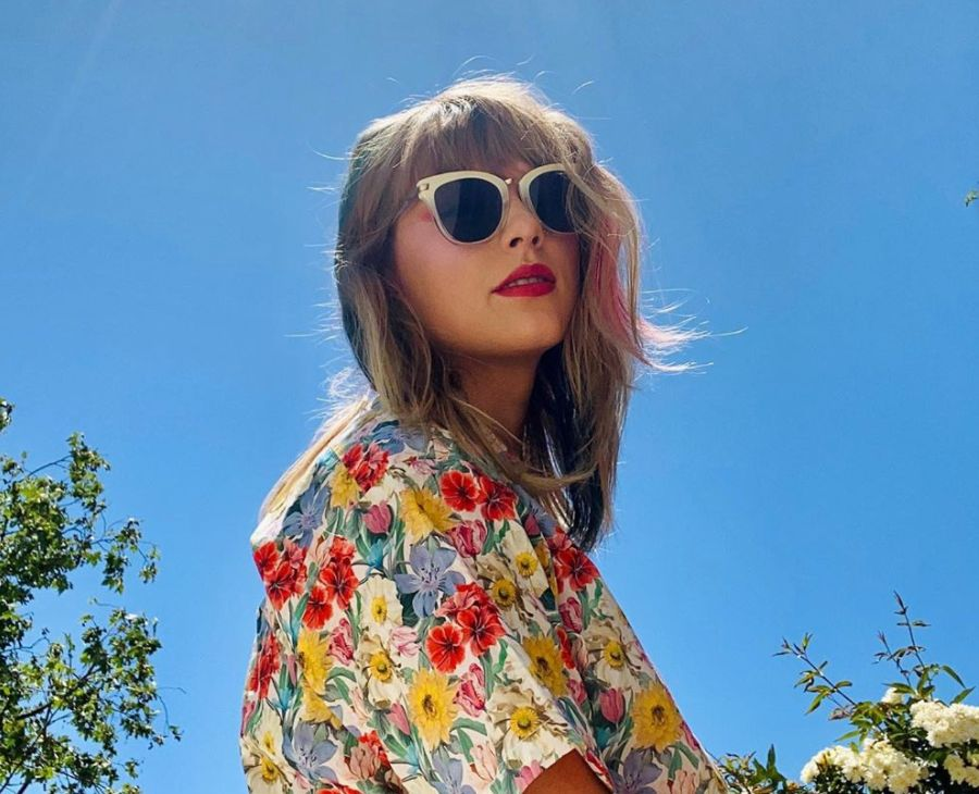Taylor Swift posing outside wearing a floral shirt.