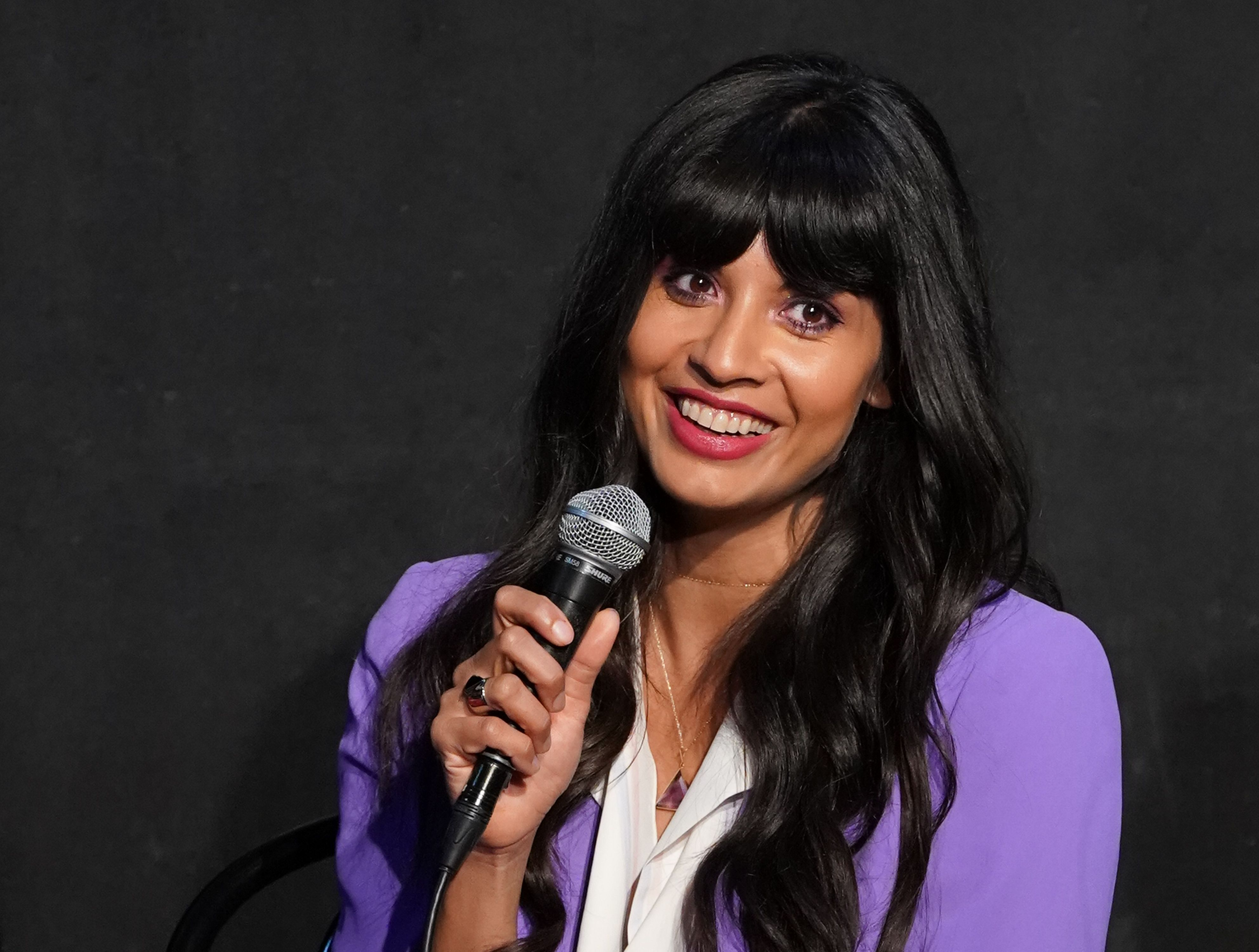 Jameela Jamil has a cute smile on her face as she holds a microphone to her mouth while addressing a crowd.