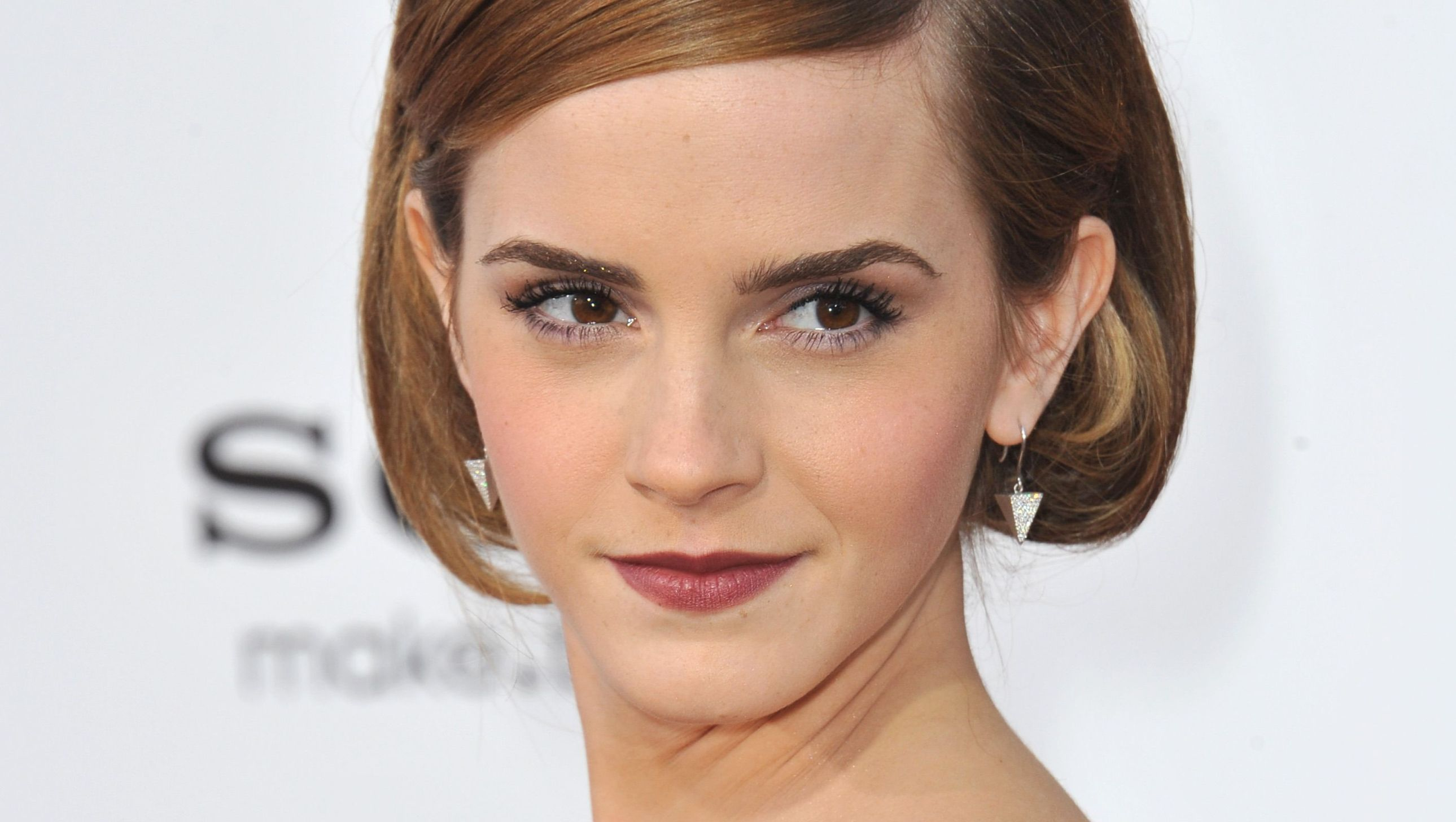 Emma Watson wears short hair and dark lipstick.