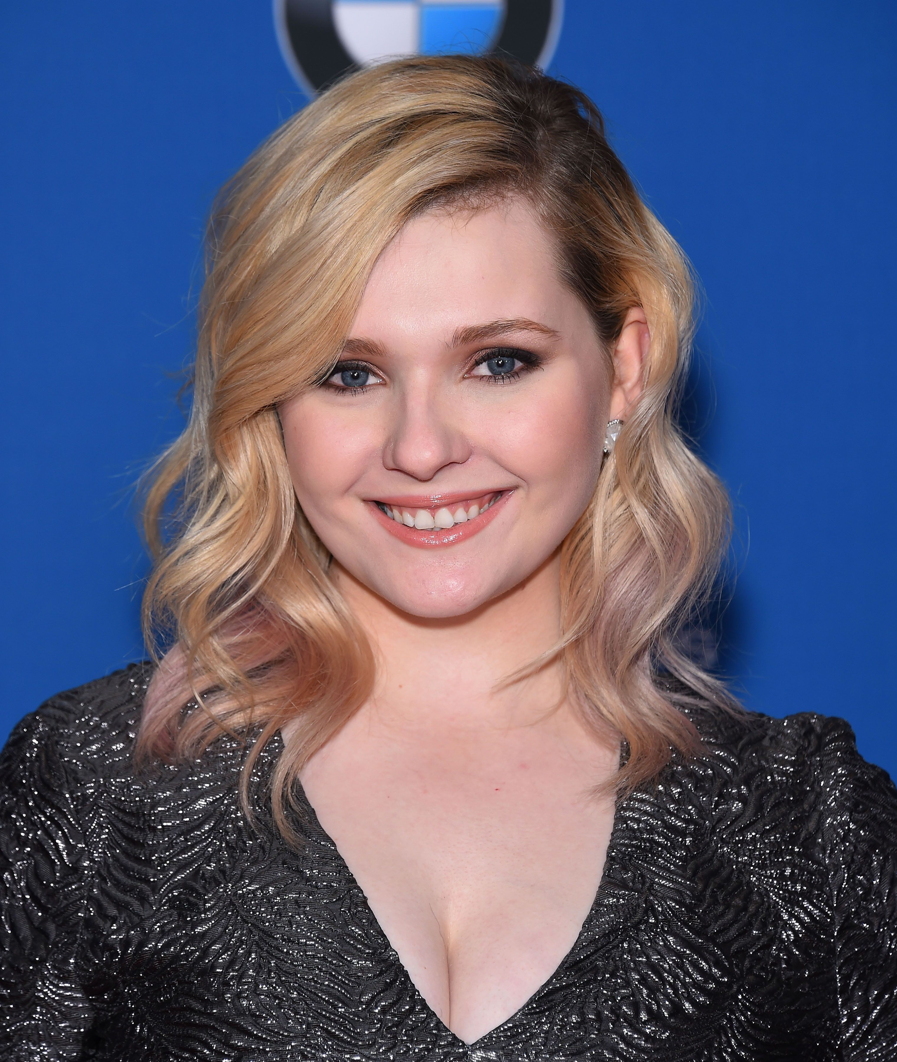 Abigail Breslin smiles as she shows off wavy blonde hair.