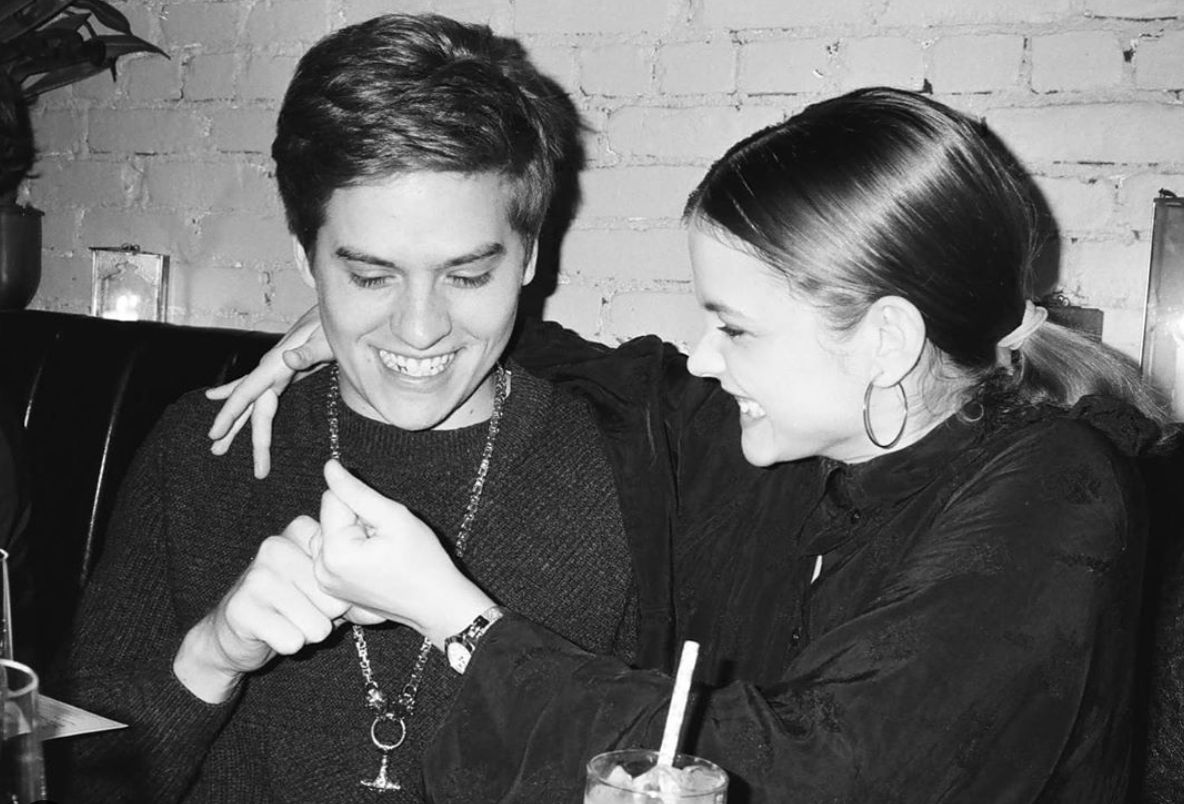 Dylan Sprouse and Barbara Palvin being playful at a restaurant table.