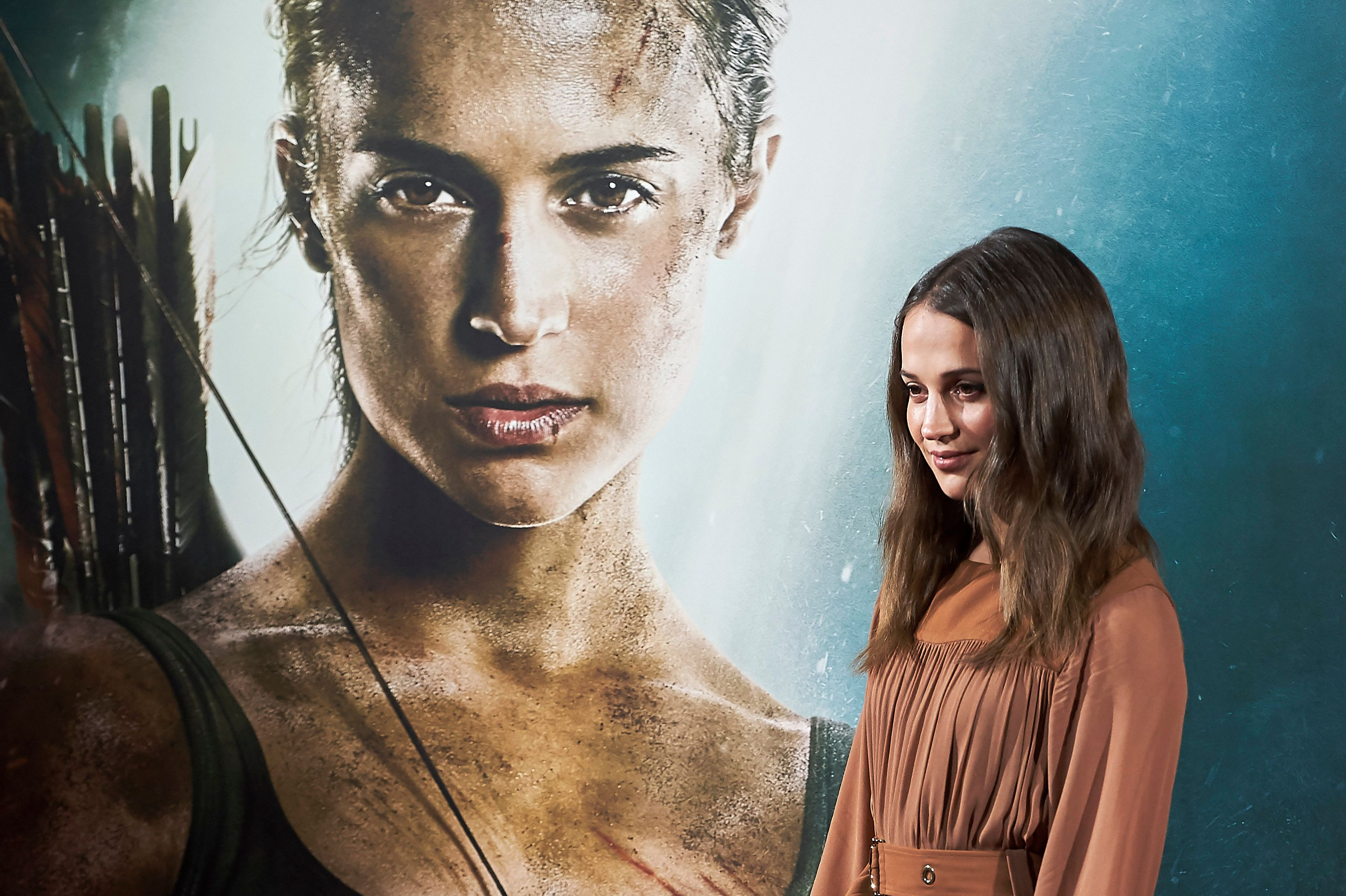 Alicia Vikander smiles in a beige dress in front of a billboard with her photo.