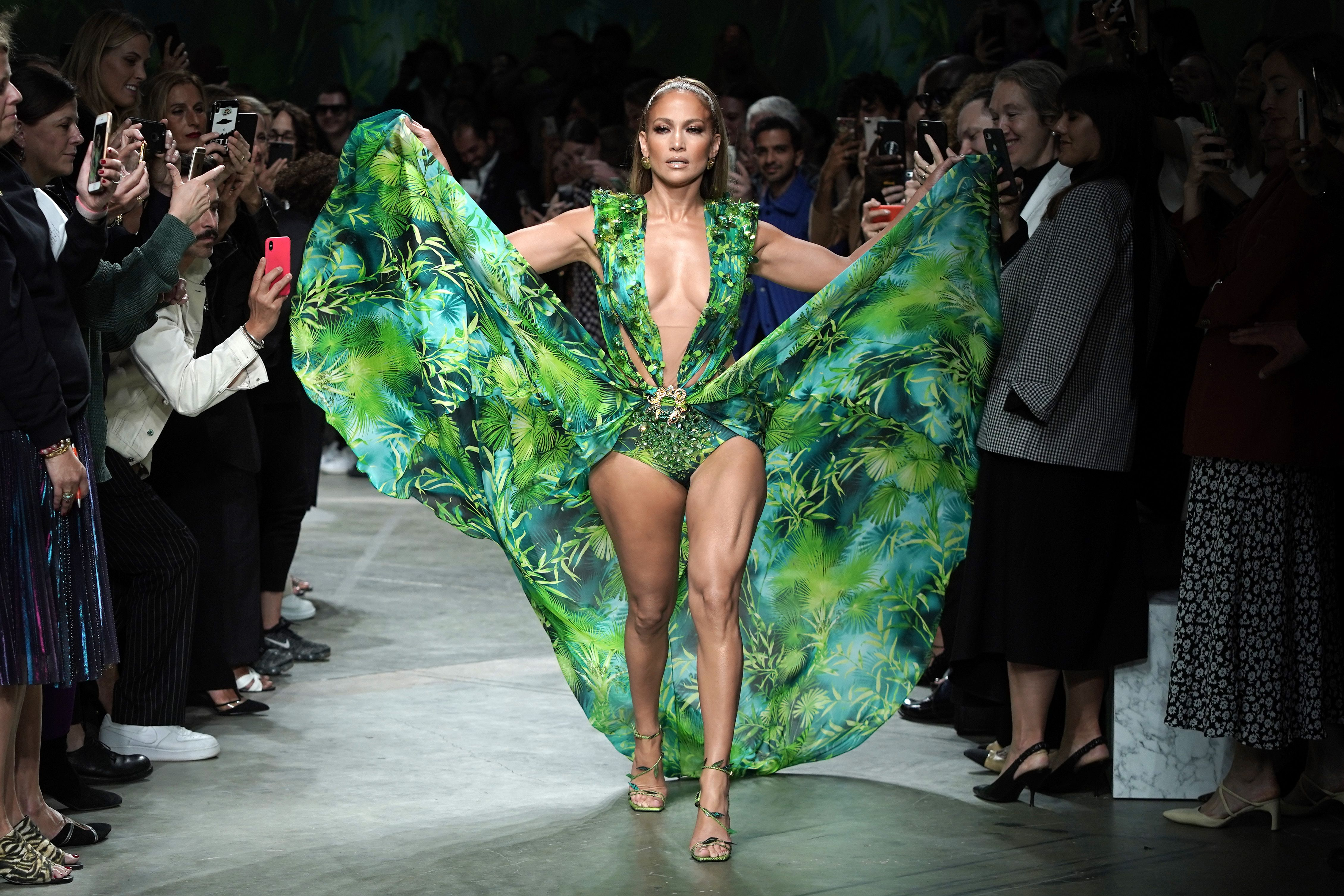 Jennifer Lopez looks incredible in this flowery green dress as she walks in the midst of people while flashing her thighs.