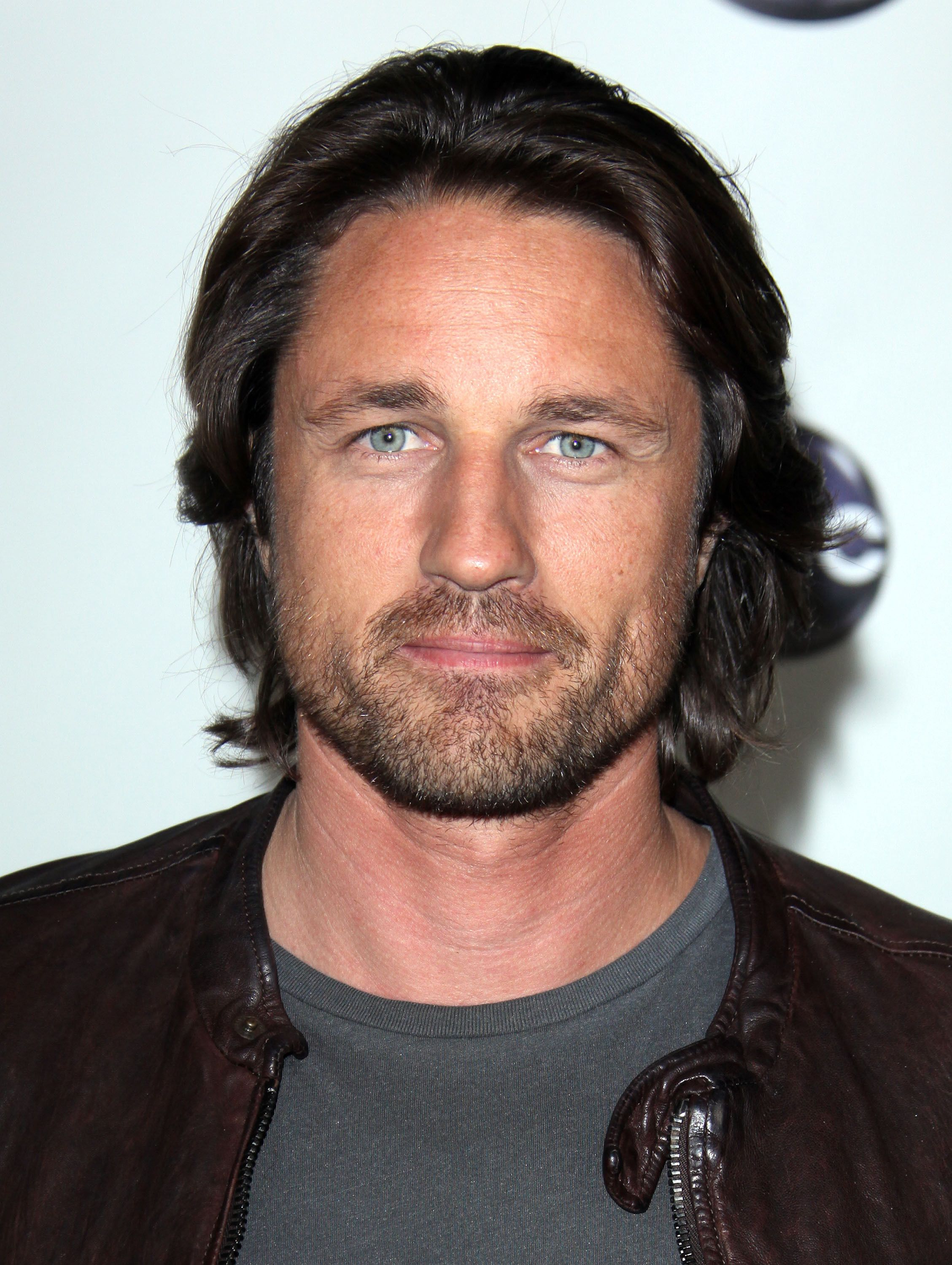 Martin Henderson wears a leather jacket and gray T-shirt.