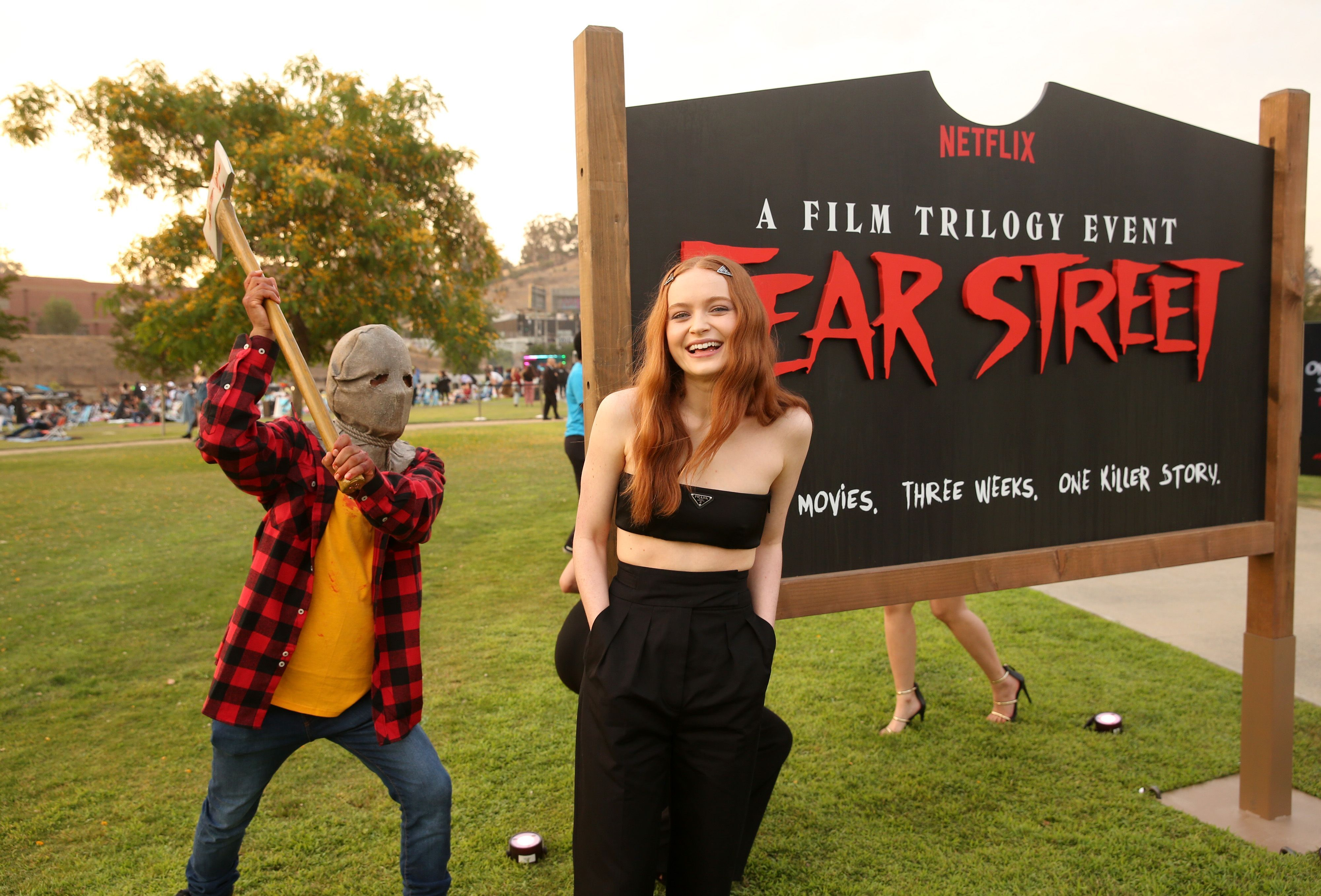 Sadie Sink stands in front of a 'Fear Street' sign with an axed man behind her.