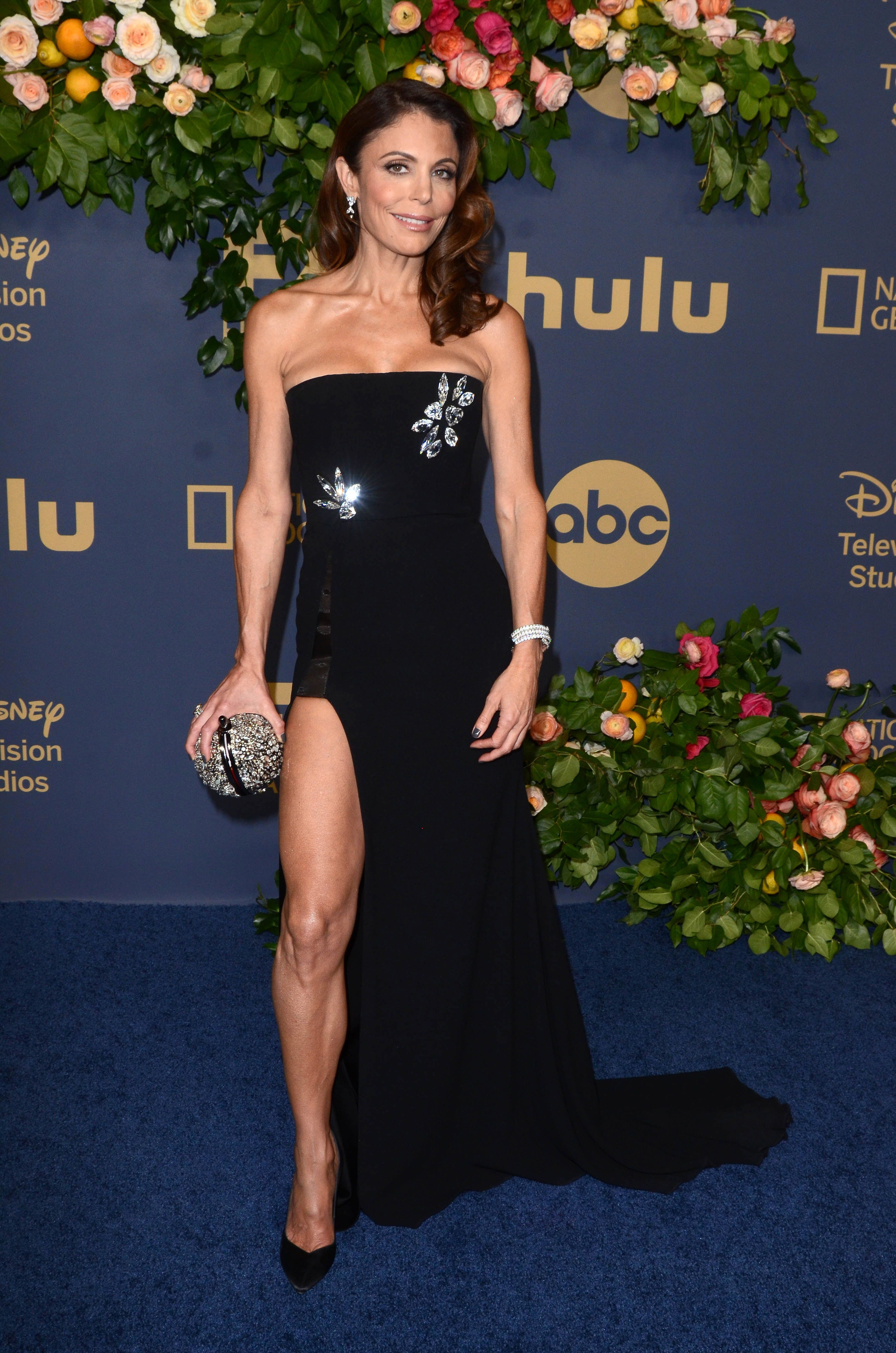 Bethenny Frankel wears a strapless gown and curled hair.