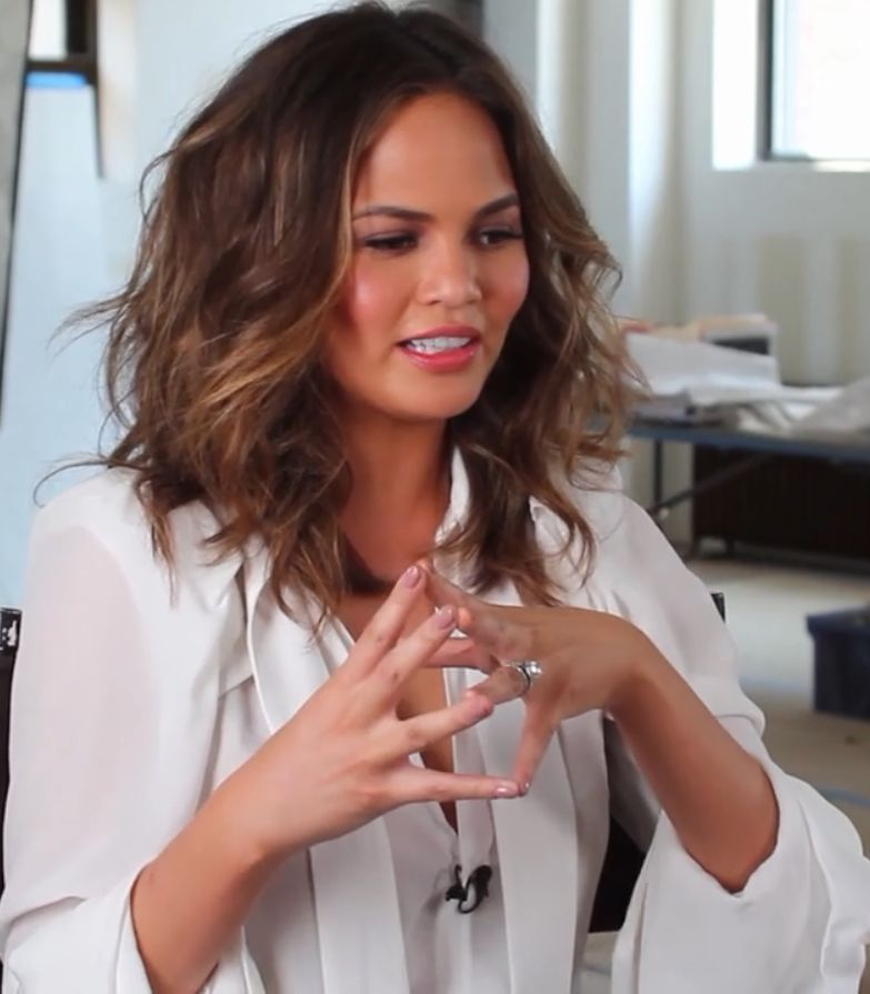 A lovely photo of Chrissy Teigen in motion showing hand gestures and she looks amazing.