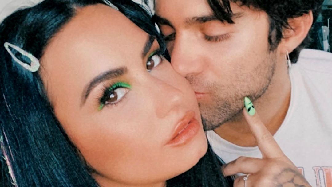 Demi Lovato shows off her alien-painted nails as boyfriend Max Ehrich kisses her cheek
