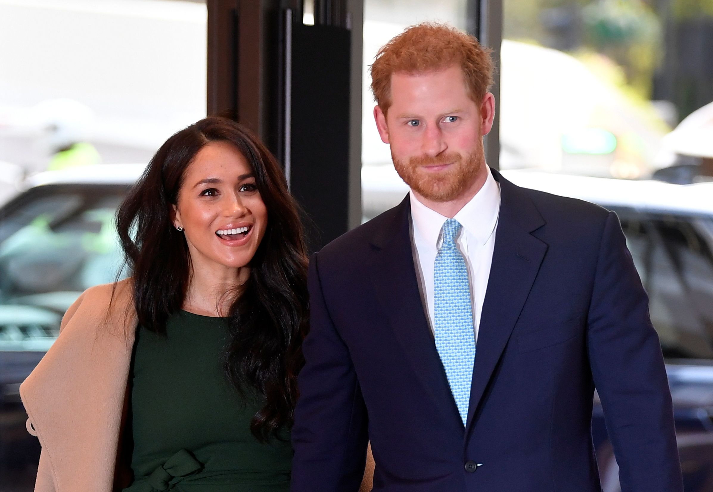 Meghan Markle and Prince Harry smiling next to each other