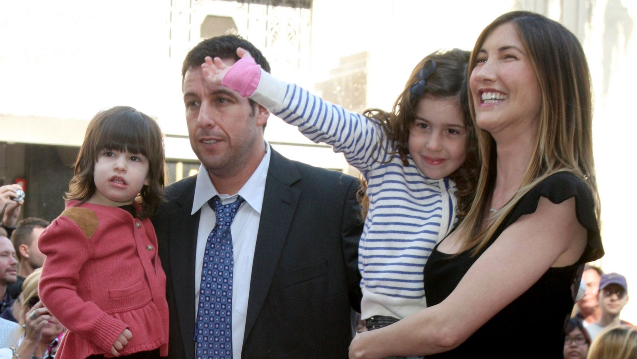 Adam and Jackie Sandler hold their two kids, Sunny and Sadie.