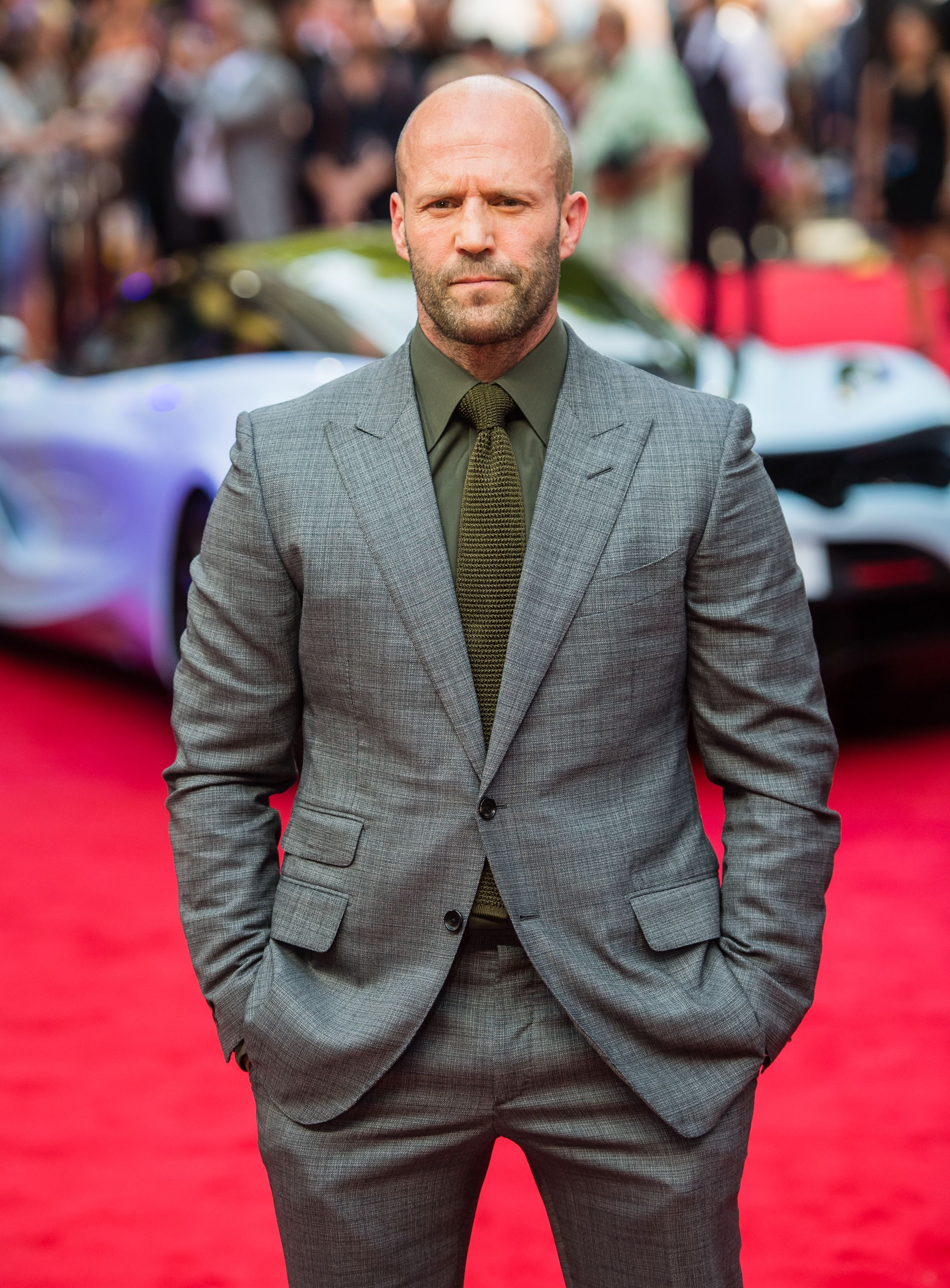 An amazing photo showing Jason Statham dressed in a well-fitted grey suit and pant at a red carpet show.