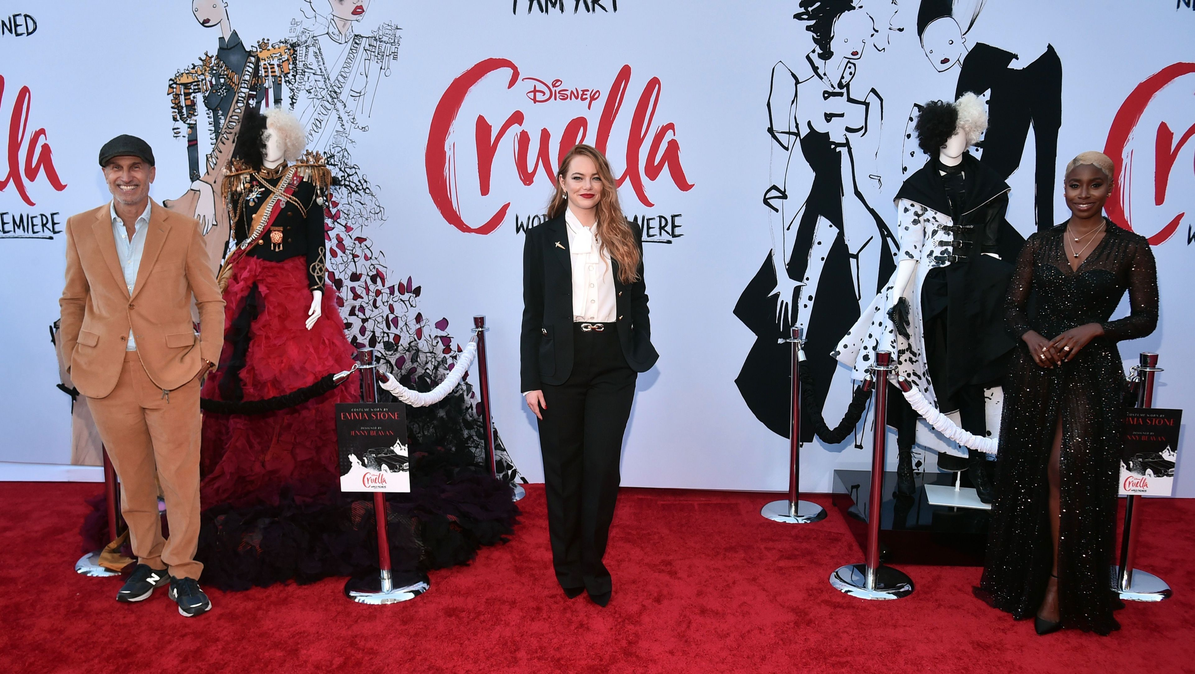 Emma Stone stands in a suit and white blouse at the 'Cruella' premiere.