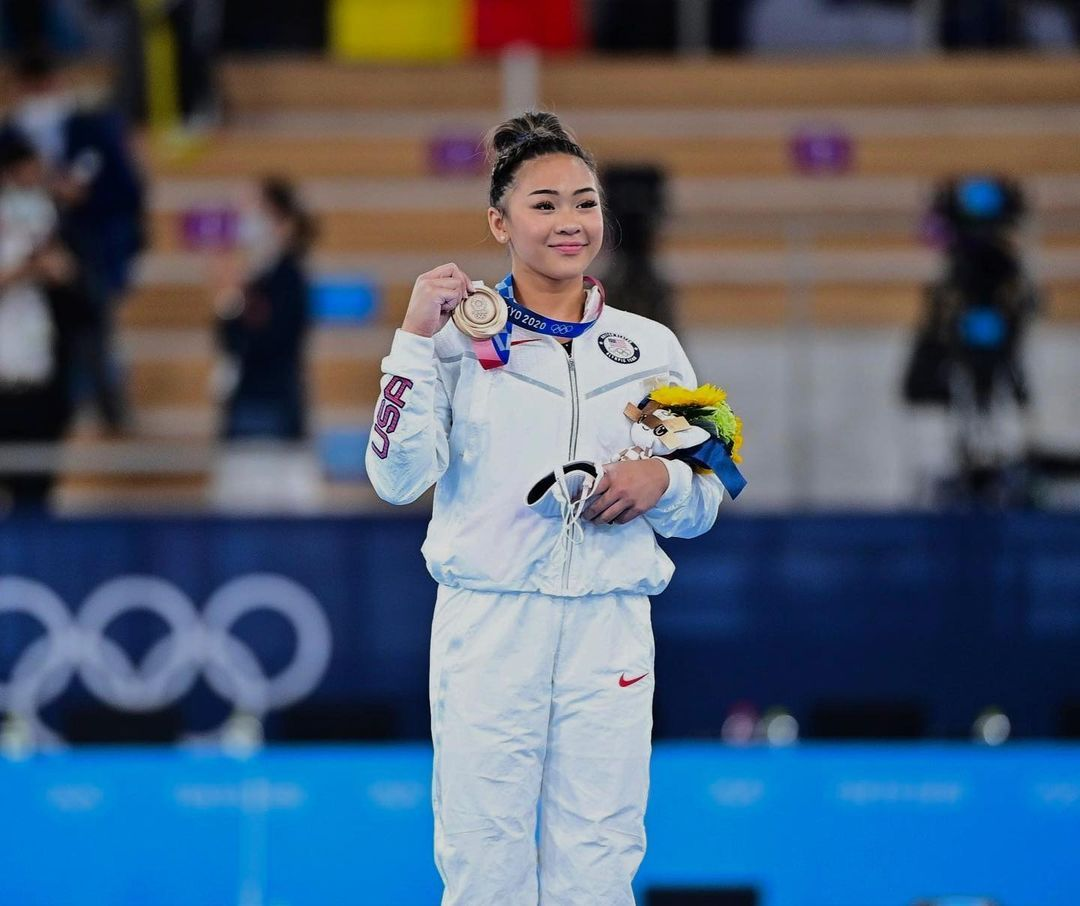 Sunisa Lee holds up a medal at the 2021 Tokyo Olympics.