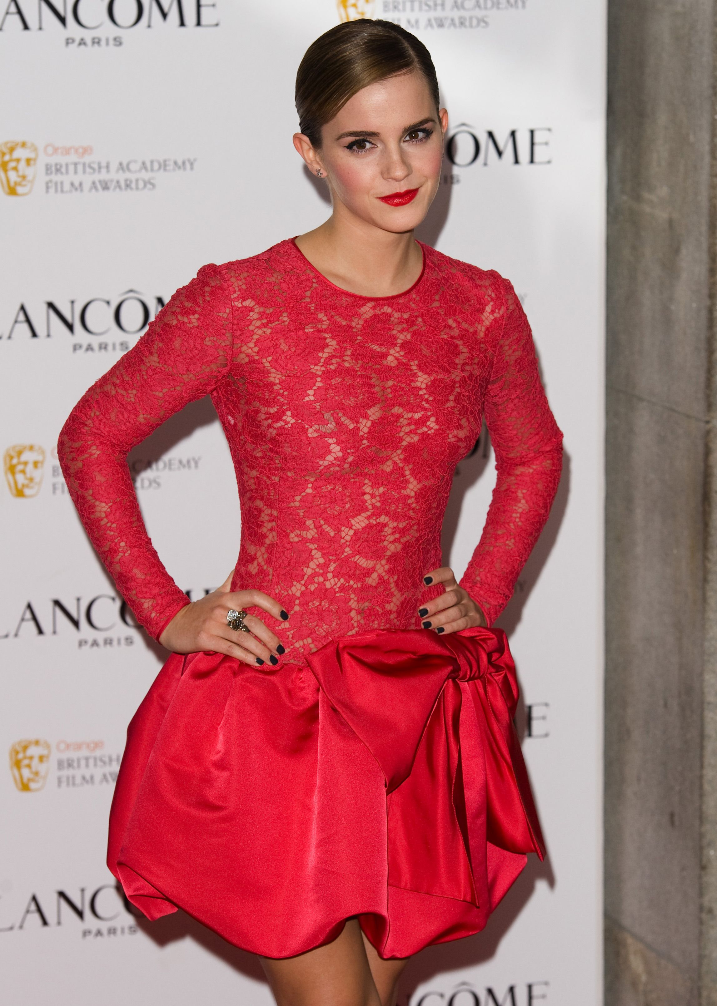 Emma Watson wears a red puffy skirt gown.