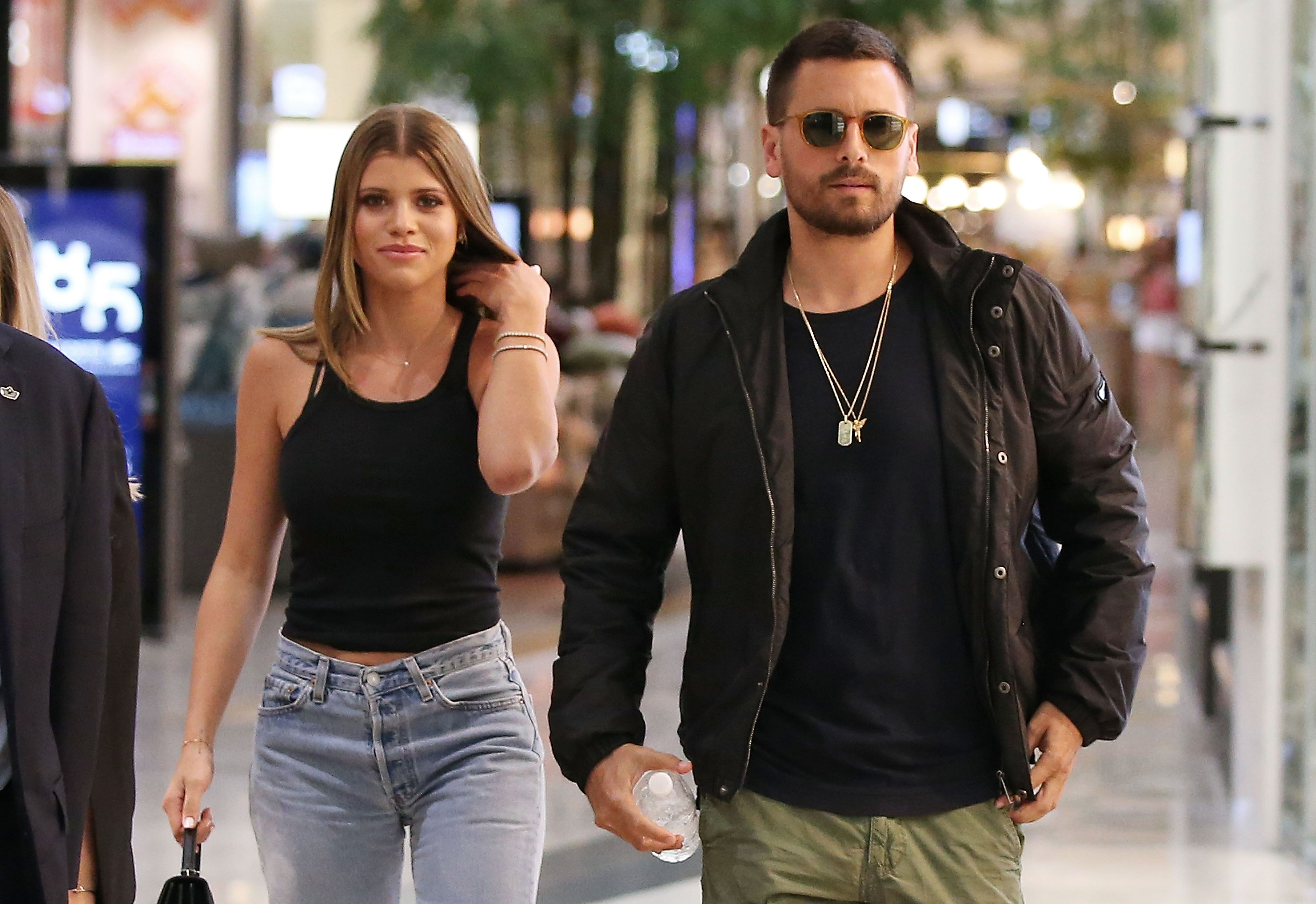 Sofia Richie and Scott Disick walking together.