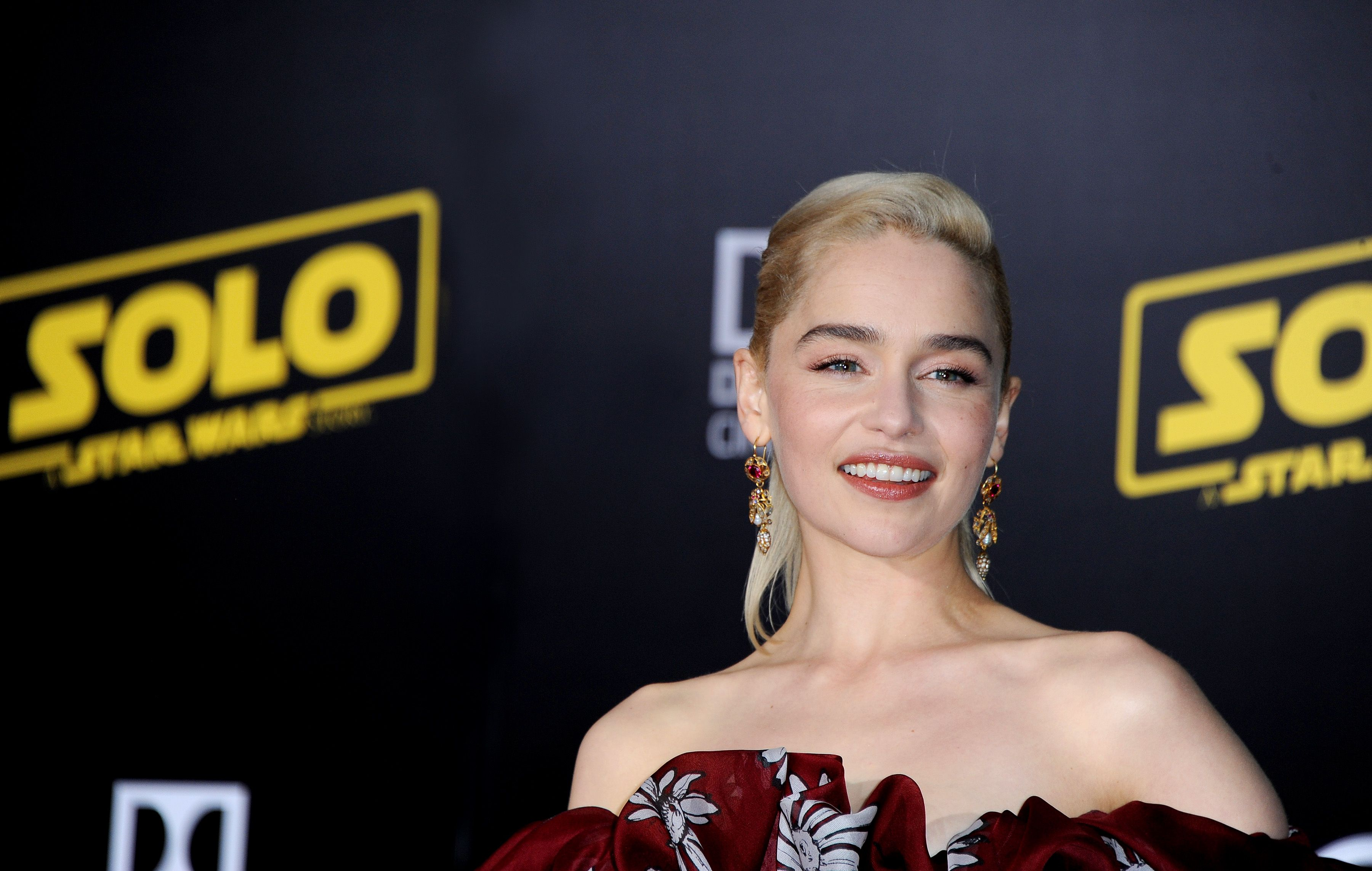 Emilia Clarke wears her hair in a ponytail with a strapless gown.