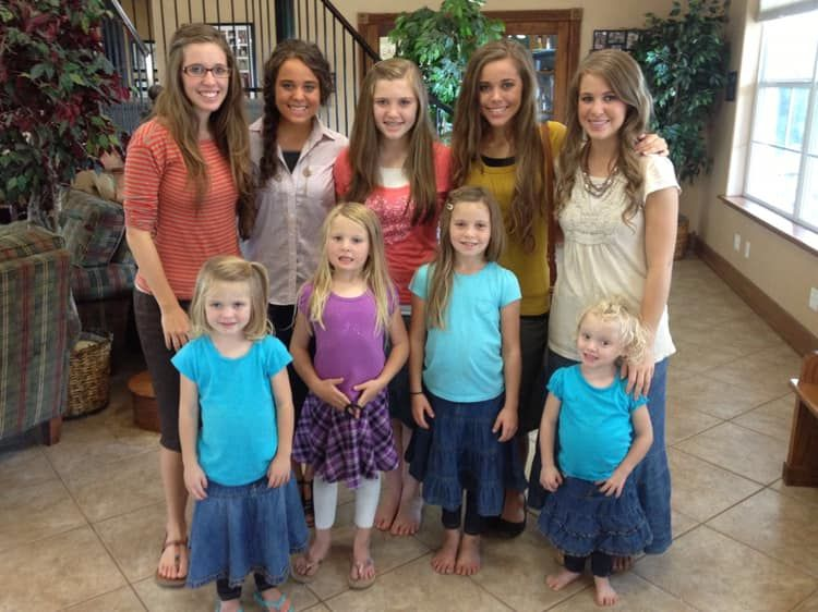 The adult Duggar daughters pose with theri younger siblings