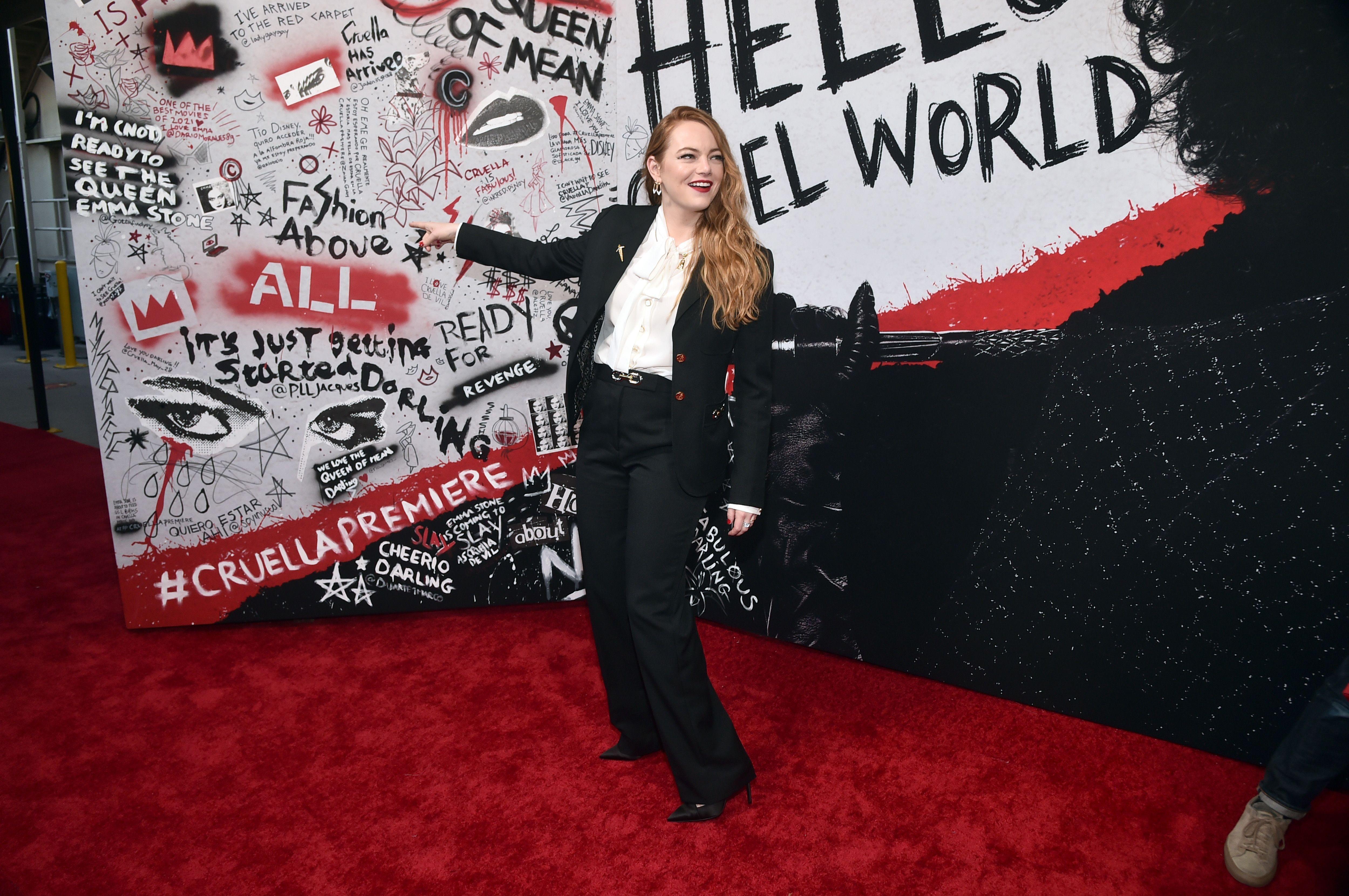 Emma Stone poses in front of a 'Cruella' billboard.