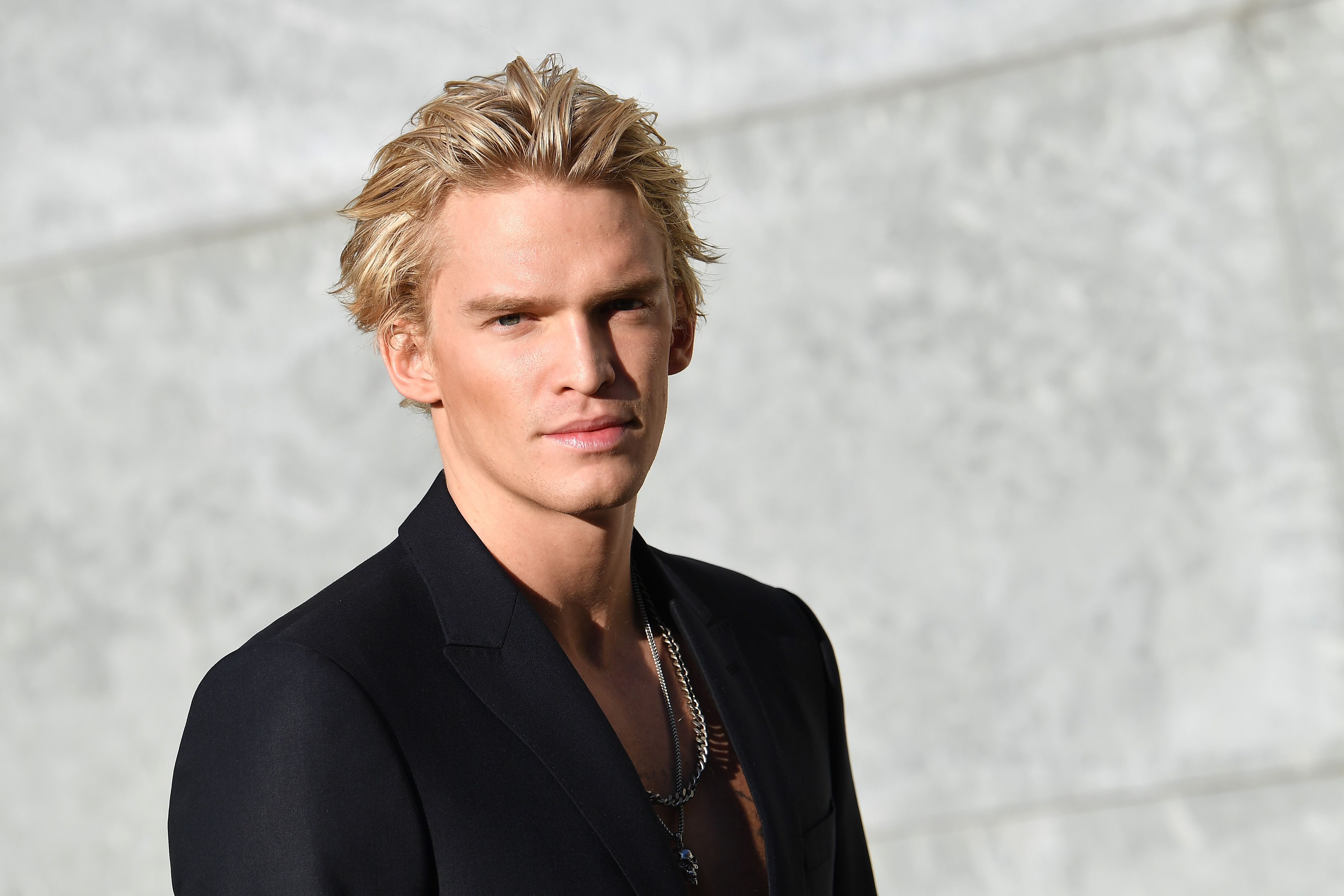 Cody Simpson smiling with a white backdrop.