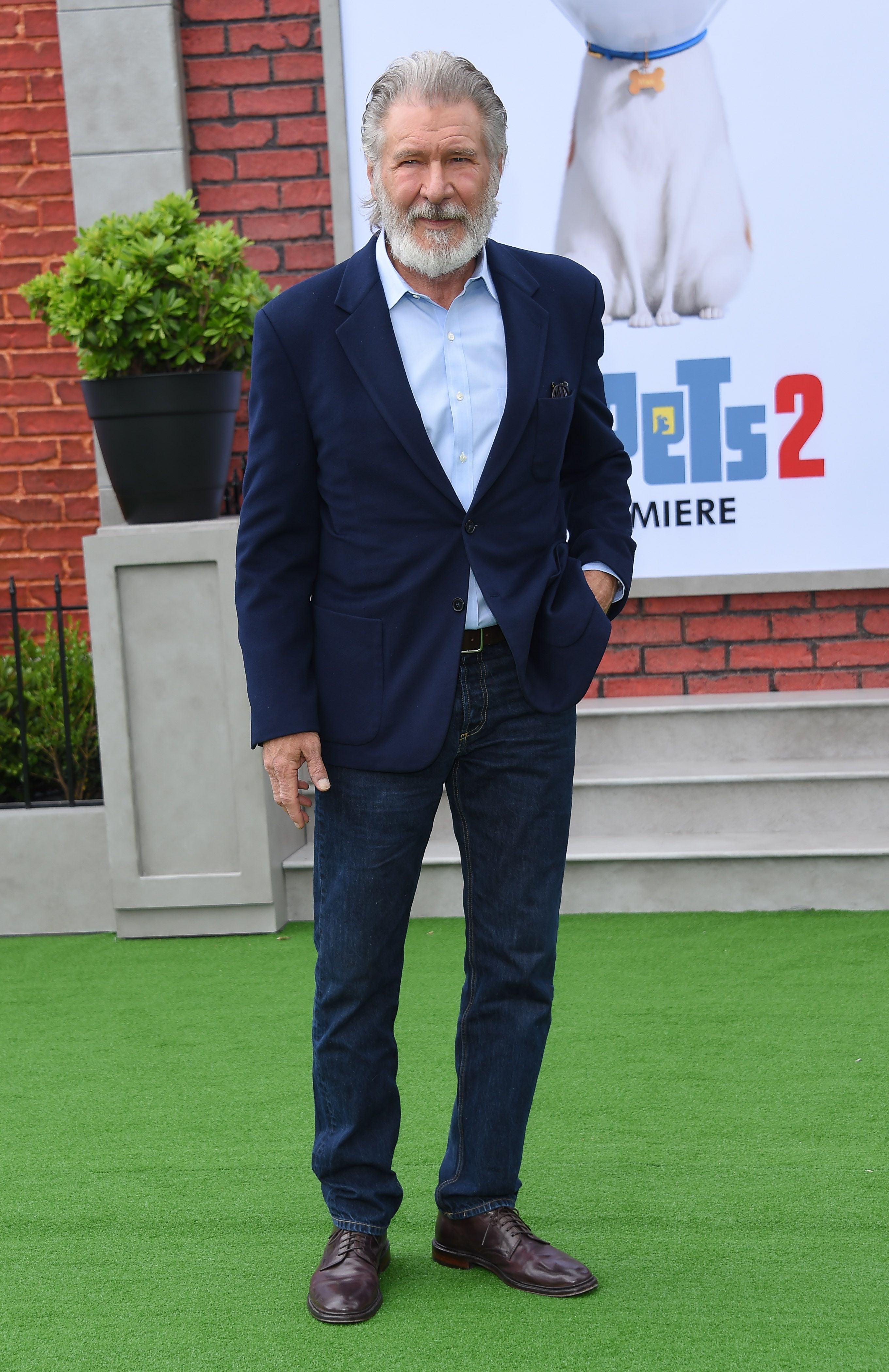 Harrison Ford with a beard in a blue blazer and jeans.
