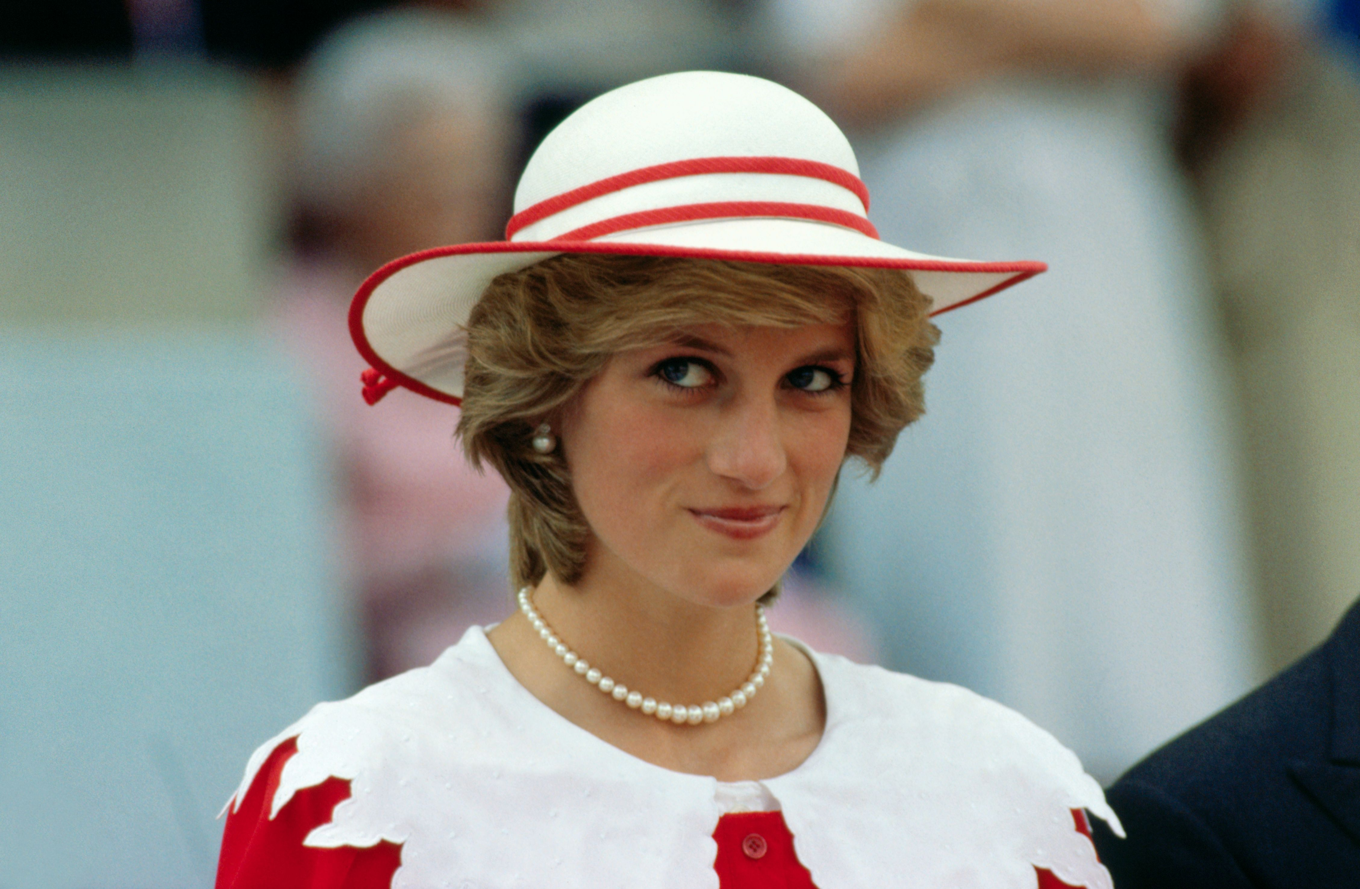 Princess DIana in a red and whte hat smiling