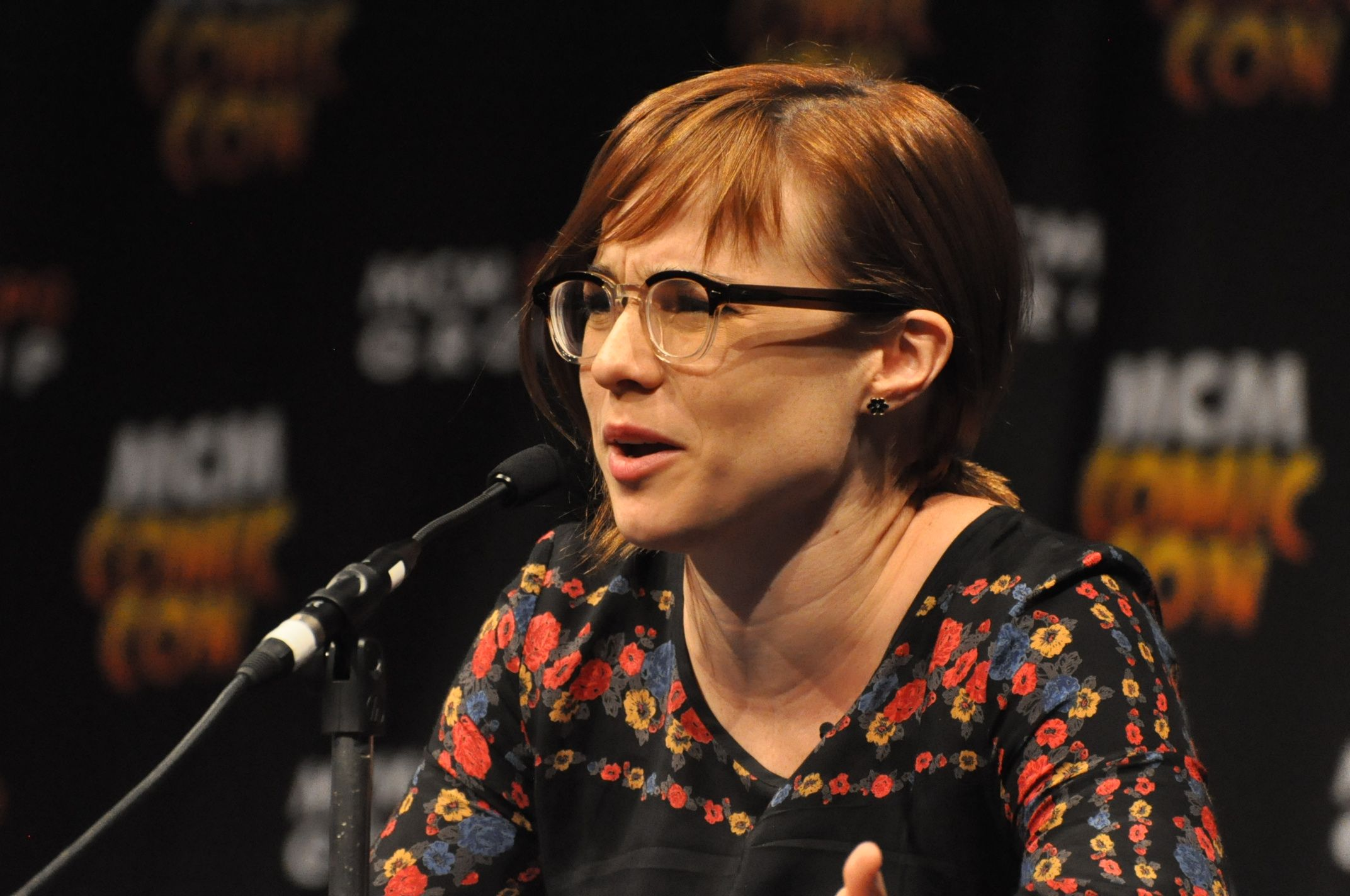 A woman with red hair speaking into a microphone.