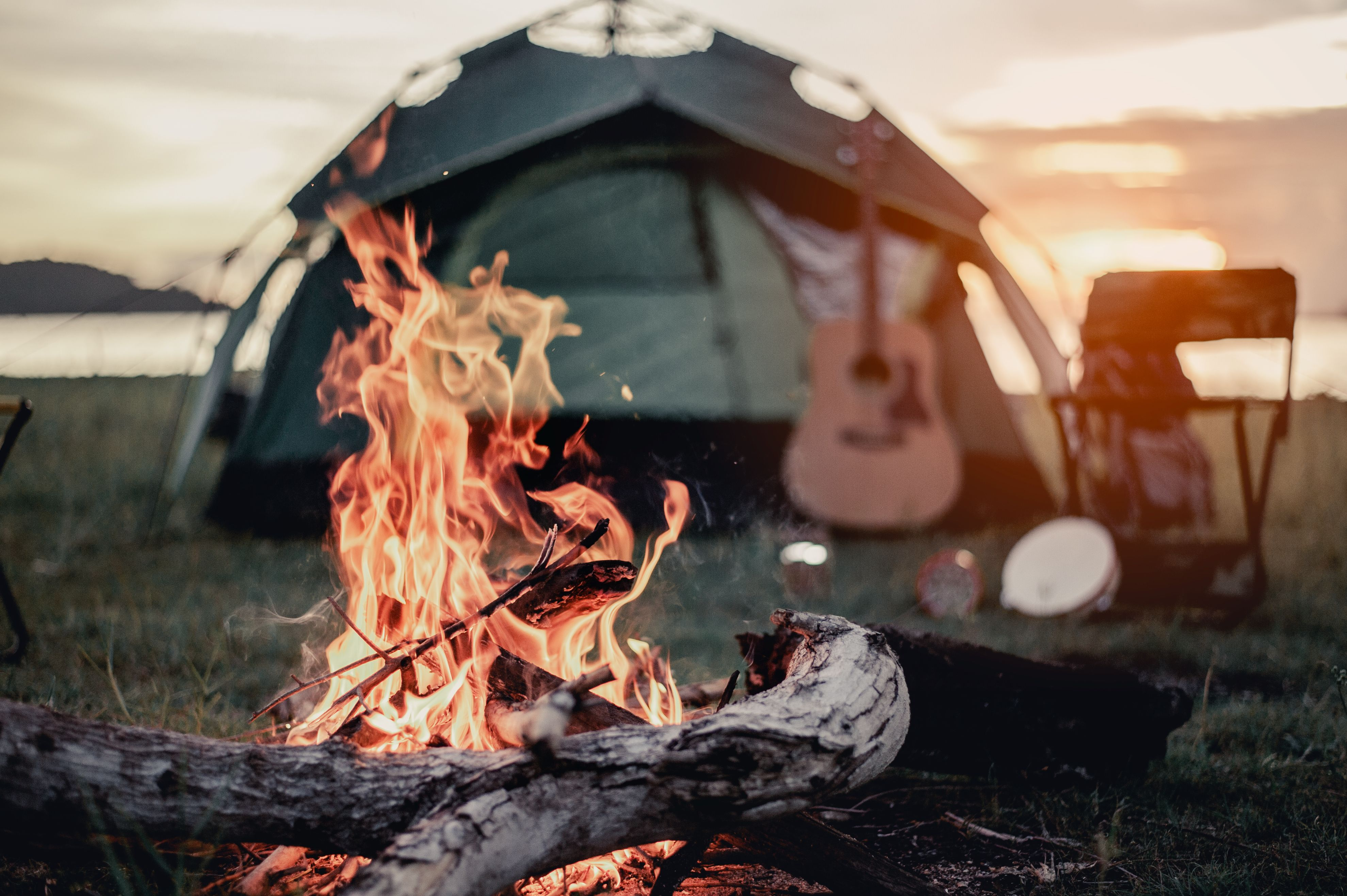 A campfire with a tent, chair, and guitar in the background.