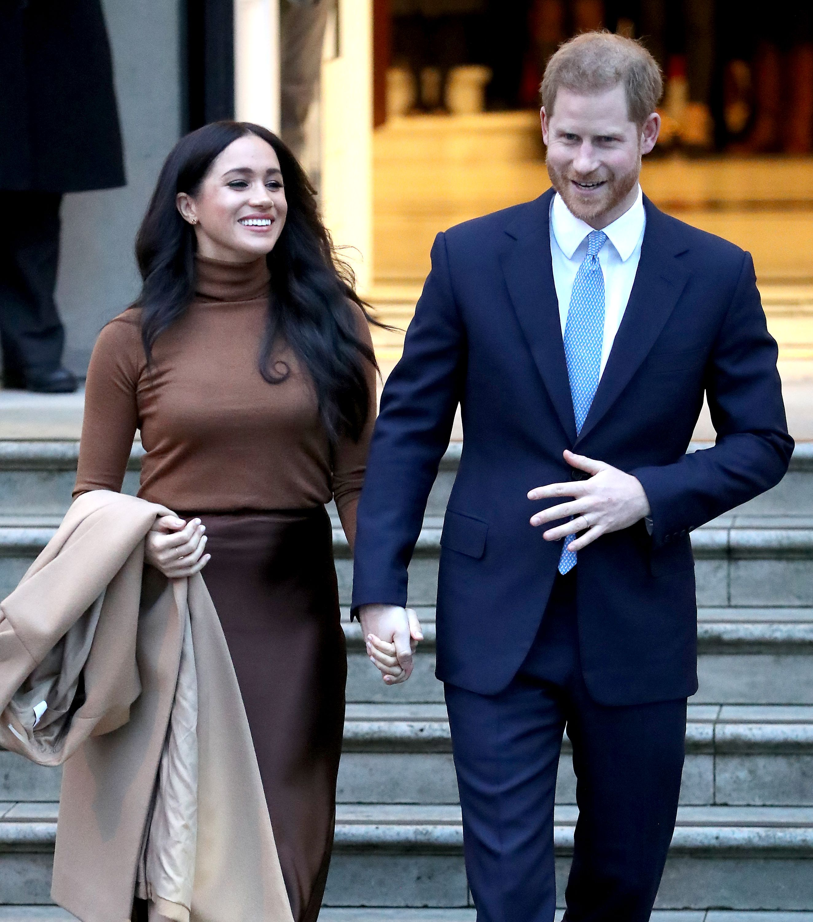 Prince Harry holding Meghan Markle's hand while they are both smiling