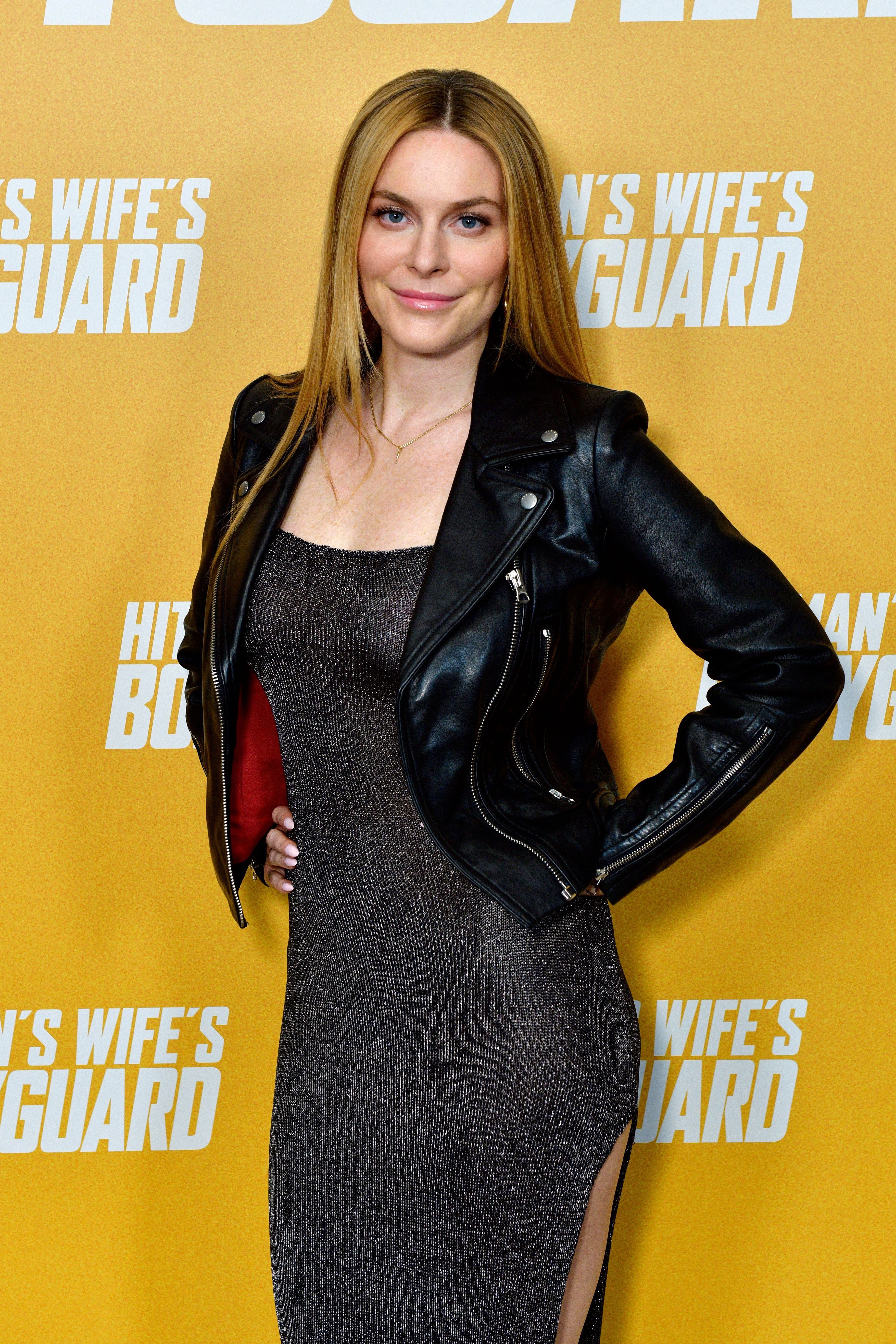 Leah McSweeney wears a black jacket over a black dress with her hair down.