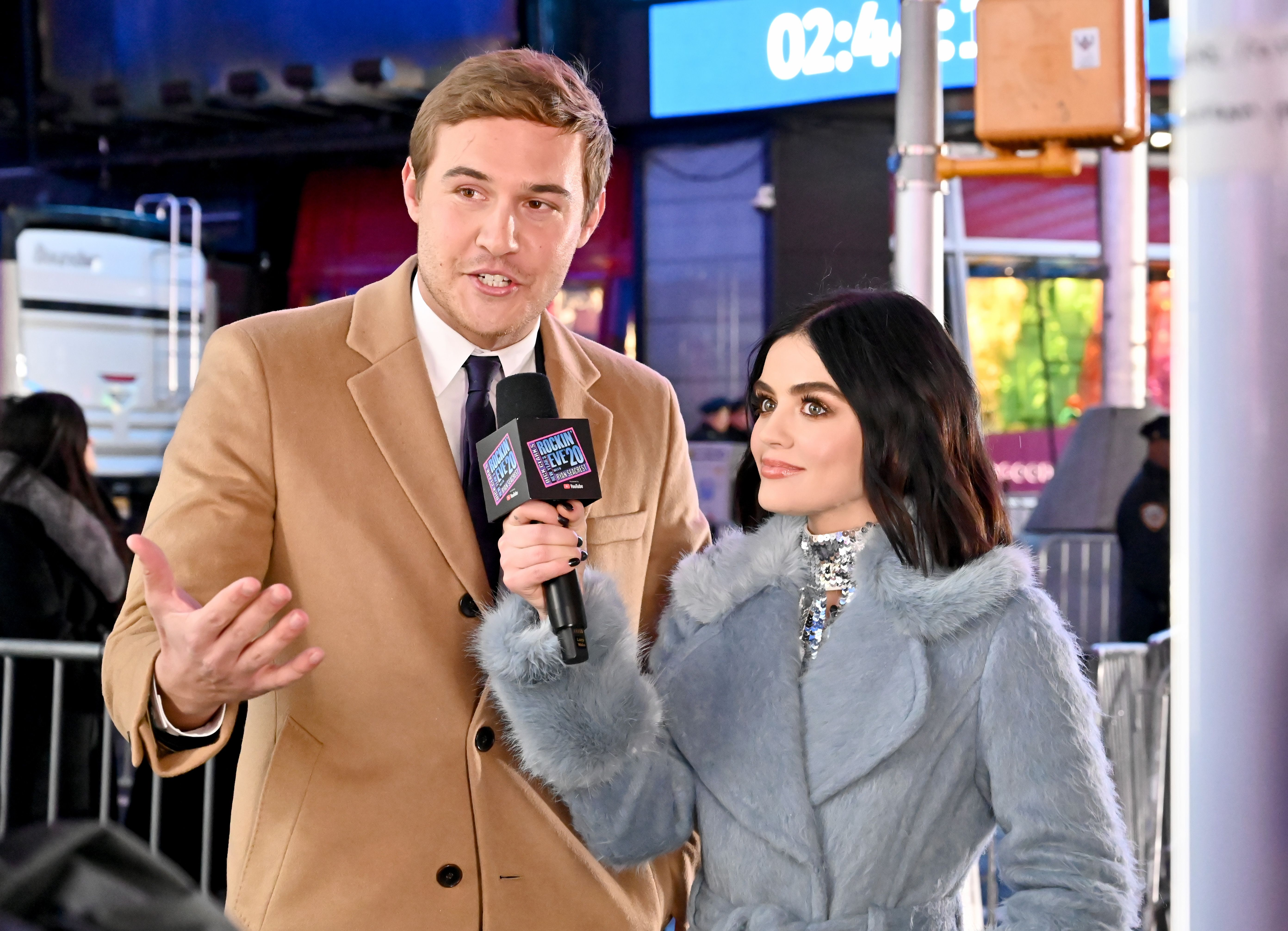 Lucy Hale (right) holds up a microphone to Peter Weber (left)