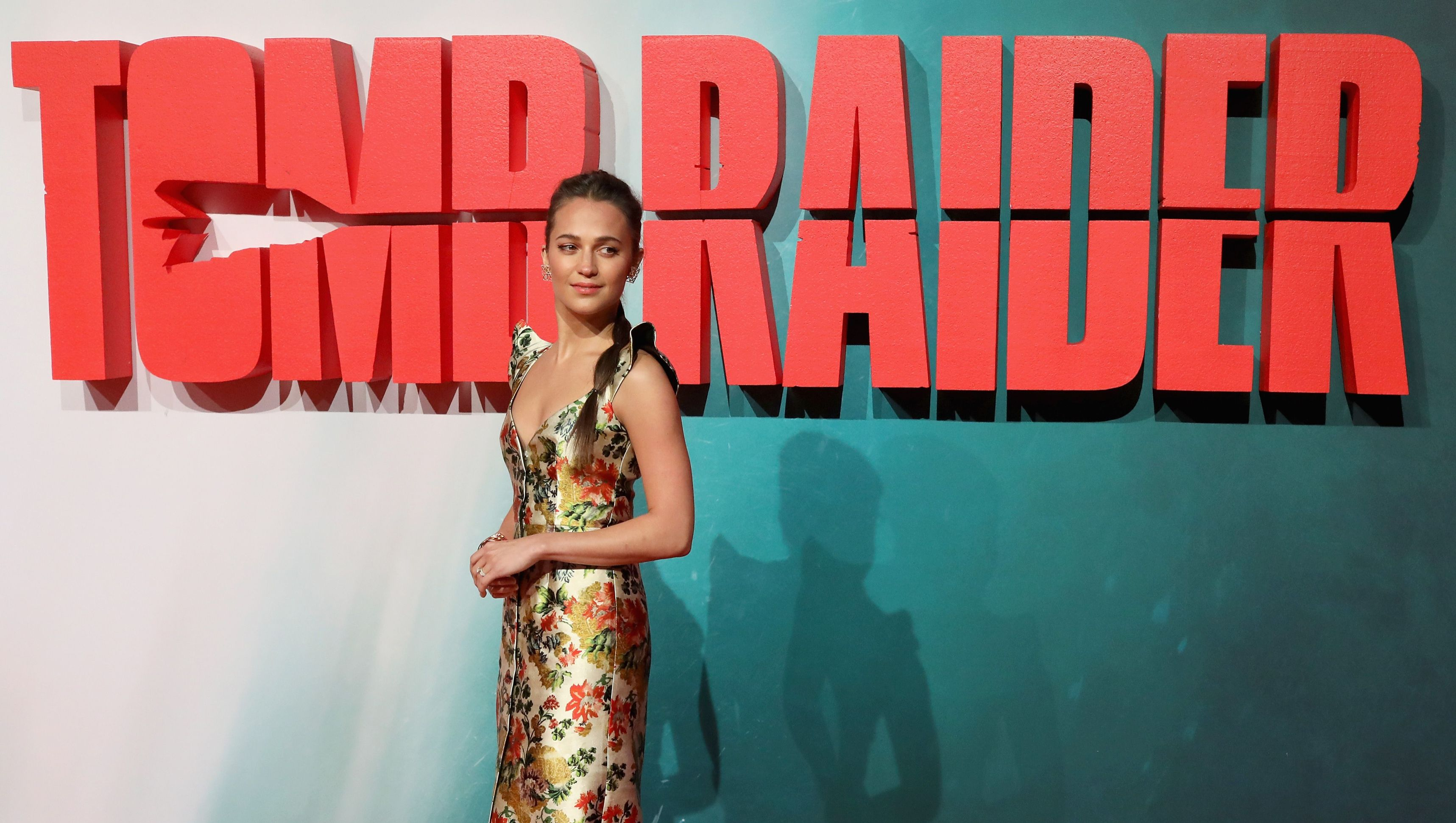 Alicia Vikander stands in a floral dress in front of a 'Tomb Raider' sign.